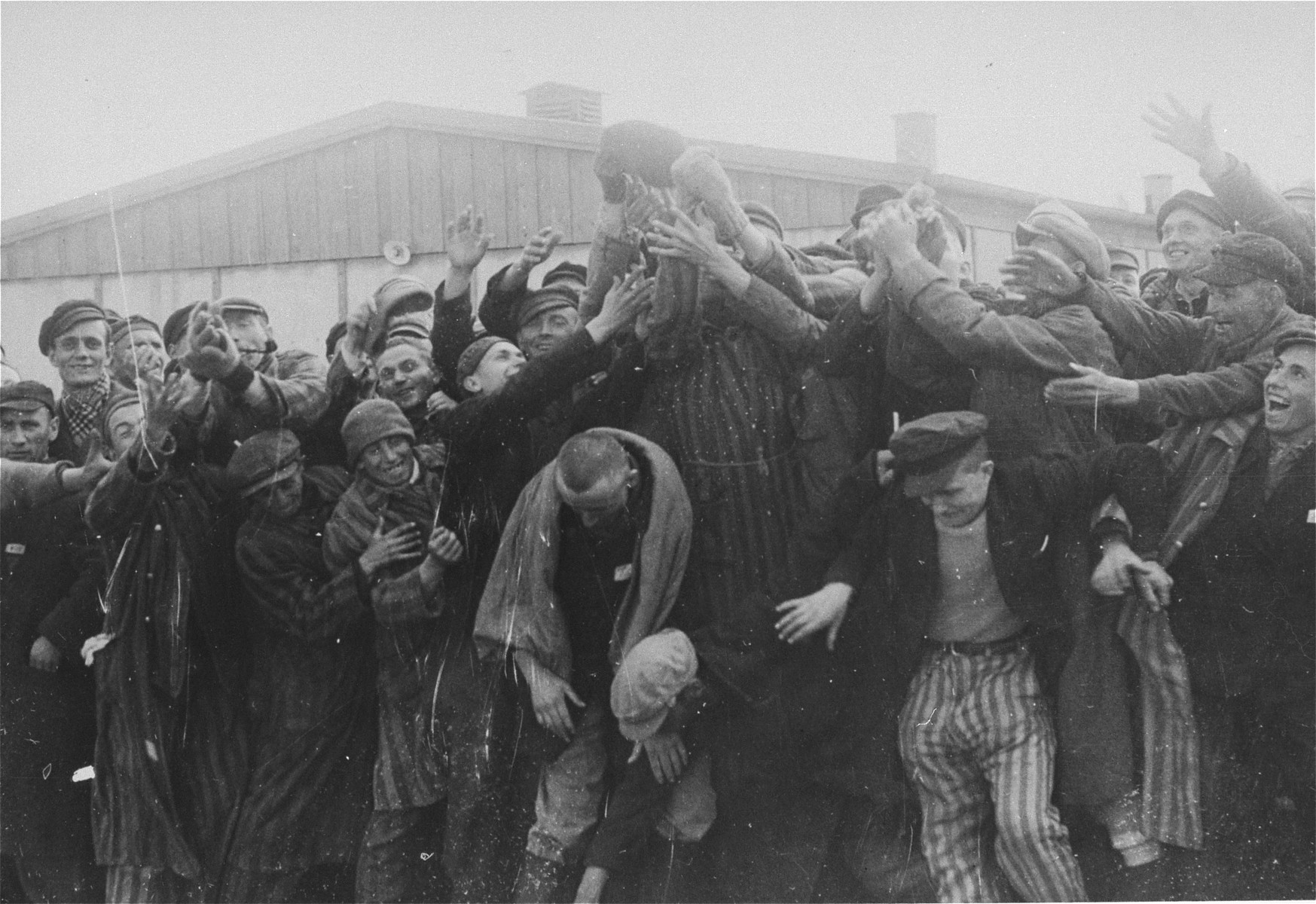 "Survivors fight for cigarettes thrown to them by American troops after the liberation of the Dachau concentration camp.  Original caption reads: ""Dachau Concentration Camp.  Horrors worse than those found in the German concentration camps of Buchenwald and Belsen were discovered in the stinking hell-hole of Dachau, captured by troops of the 42nd and 45th Infantry Divisions of the Seventh U.S. Army April 30, 1945.  More than 32,000 prisoners were liberated, among them some Englishmen, Canadians and Americans.  The camp was formally surrendered by an SS lieutenant carrying a white flag, accompanied by a Swiss Red Cross official, but SS troops opened fire as American troops approached the main entrance.  The Germans were shot down.  Three prisoners were electrocuted when they tried to burst through the electrified wire barrier to welcome the Americans.  SS guards opened fire on other prisoners who went wild with joy and rushed to meet the liberating troops.  Prisoners with access to records said 9,000 people died of hunger, disease or shooting within the past three months at Dachau.  Four thousand more perished during cold Winter months.  When Americans entered the camp, they found 50 open railway cars standing on a siding, apparently full of dirty clothing but actually found to contain hundreds of corpses piled on top of each other.  They also found a row of kennels where fierce dogs were kept to set after escaping men.  They discovered gas extermination chambers, incinerators full of naked bodies, bodies marked for dissection and the bodies of several small children.    This photo shows: Liberated prisoners scramble for cigarettes thrown to them by men of the Seventh U.S. Army.  Many still wear the striped uniforms of the prison."""