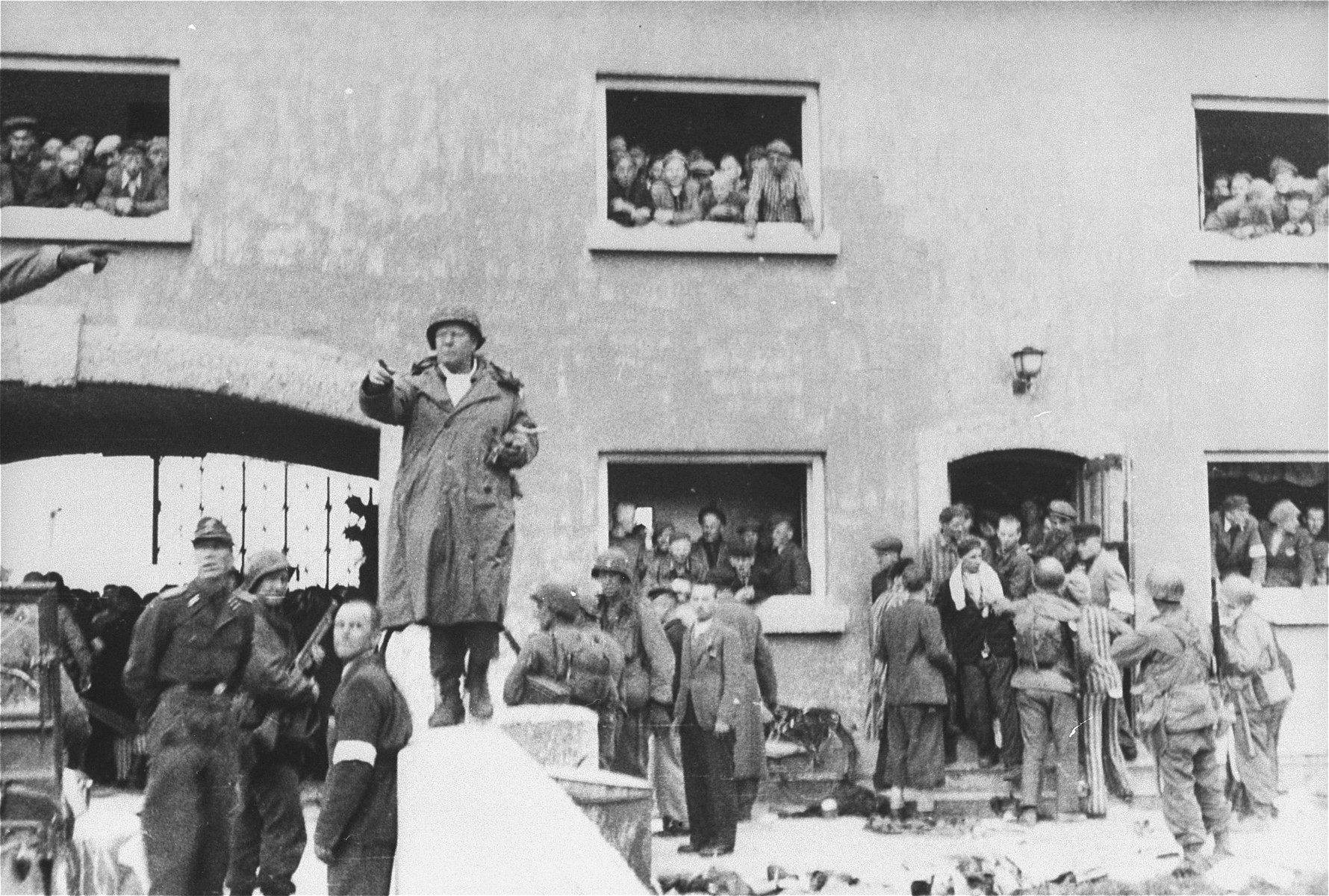 General Henning Linden, assistant commanding general, 42nd Rainbow Infantry Division, gives directions to his troops from the parapet of the bridge at the Jourhaus at the entrance to the Dachau concentration camp.  The civilian with the white armband is Dr. Victor Maurer of the ICRC (International Red Cross).  The German officer to the left is SS Lt. Wickert, the German officer who surrendered the camp. [oversize print]