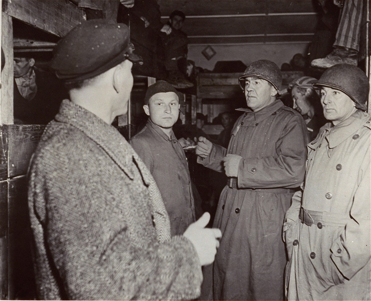 U.S. Representative John M. Vorys (R.-Ohio), (center) a member of a U.S. Congressional committee investigating German atrocities, views overcrowded conditions in the barracks which led to the deaths of many of the inmates from disease.