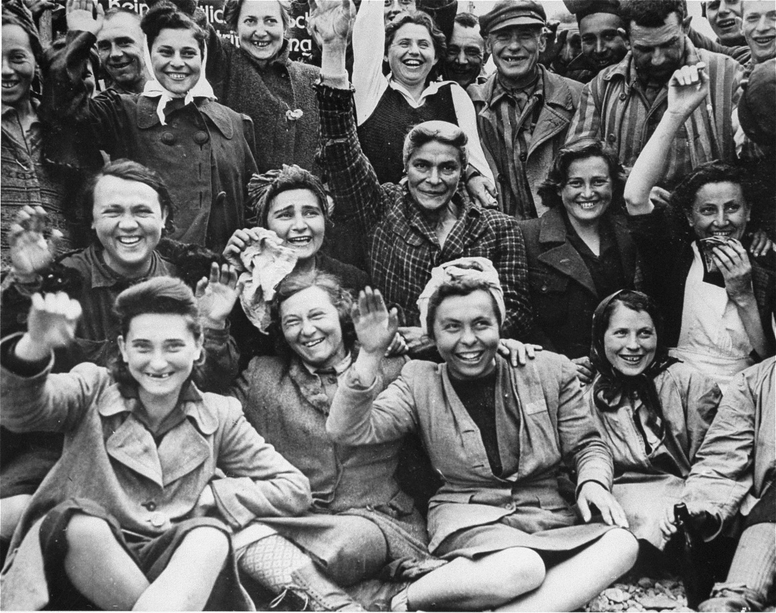 "Liberated female prisoners at Dachau wave to their liberators. [oversized print]  Original caption reads, ""Some of the women prisoners of the Dachau concentration camp laugh or cry uncontrolably at the thought of being free after years of confinement."""