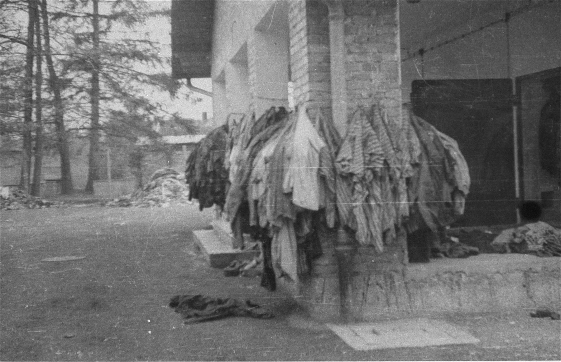 Prisoners' uniforms hung up outside a camp building.