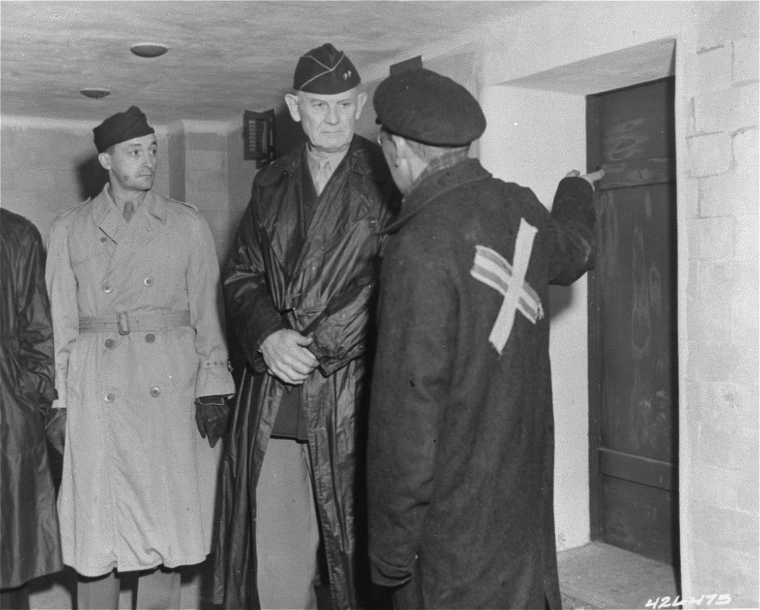 A survivor acting as a guide explains the working of a gas chamber in Dachau to Major General William R. Arnold (center), Chief of Chaplains Corps, Seventh US Army.