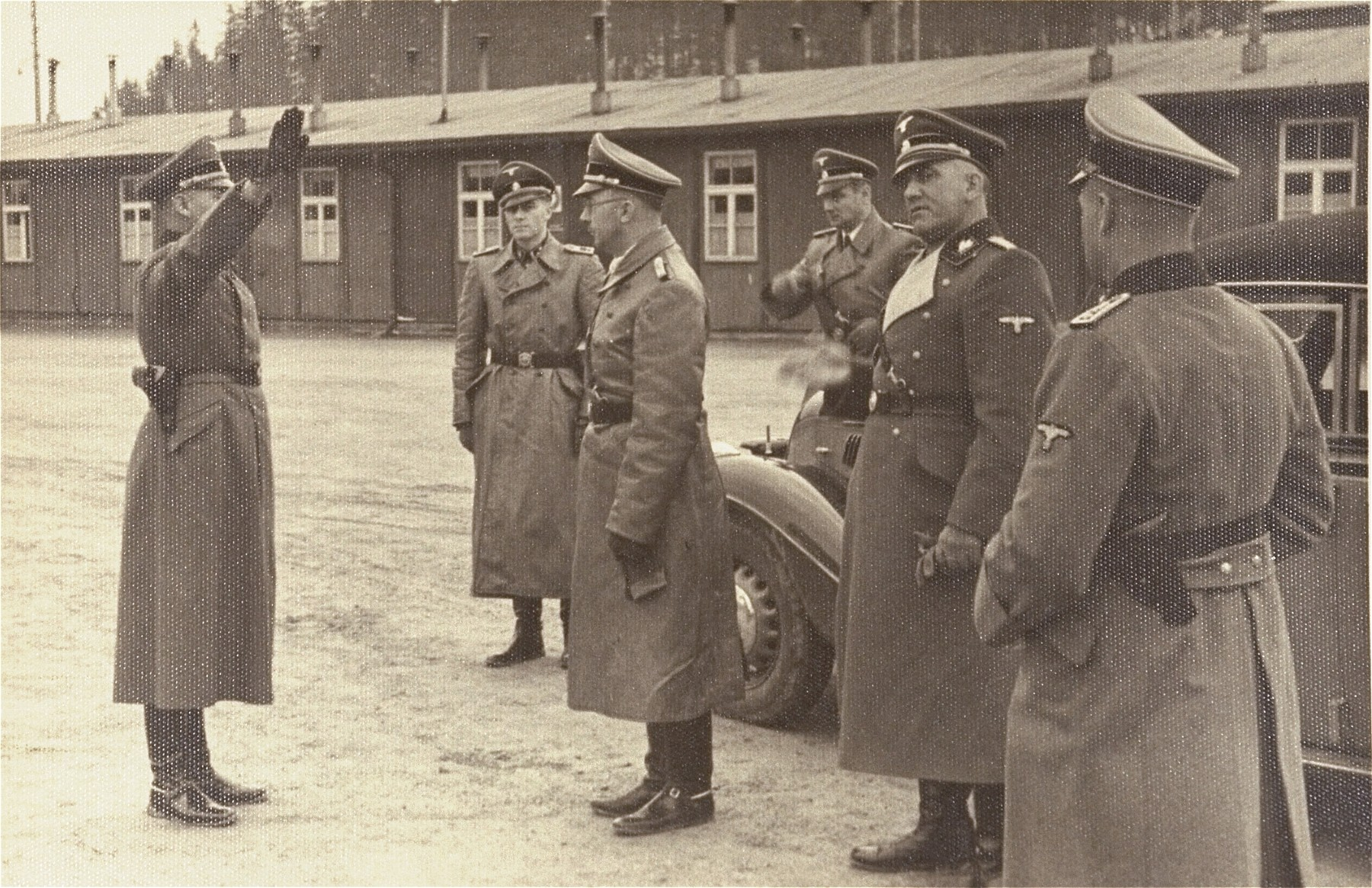 Reichsfuehrer SS Heinrich Himmler is saluted upon his arrival in Dachau for an official visit by Anton Mussert, leader of the Dutch Nazi movement.  [Man saluting has also been identified as SS Hauptsturmfuehrer Alex Piorkowski and Camp Commandant Max Koegel.]  Among those pictured is Rudolf Hoess (second from the left) [has also been identified as Joachim Peiper], [Karl Wolff] (fourth from left), and Oswald Pohl (second from the right).
