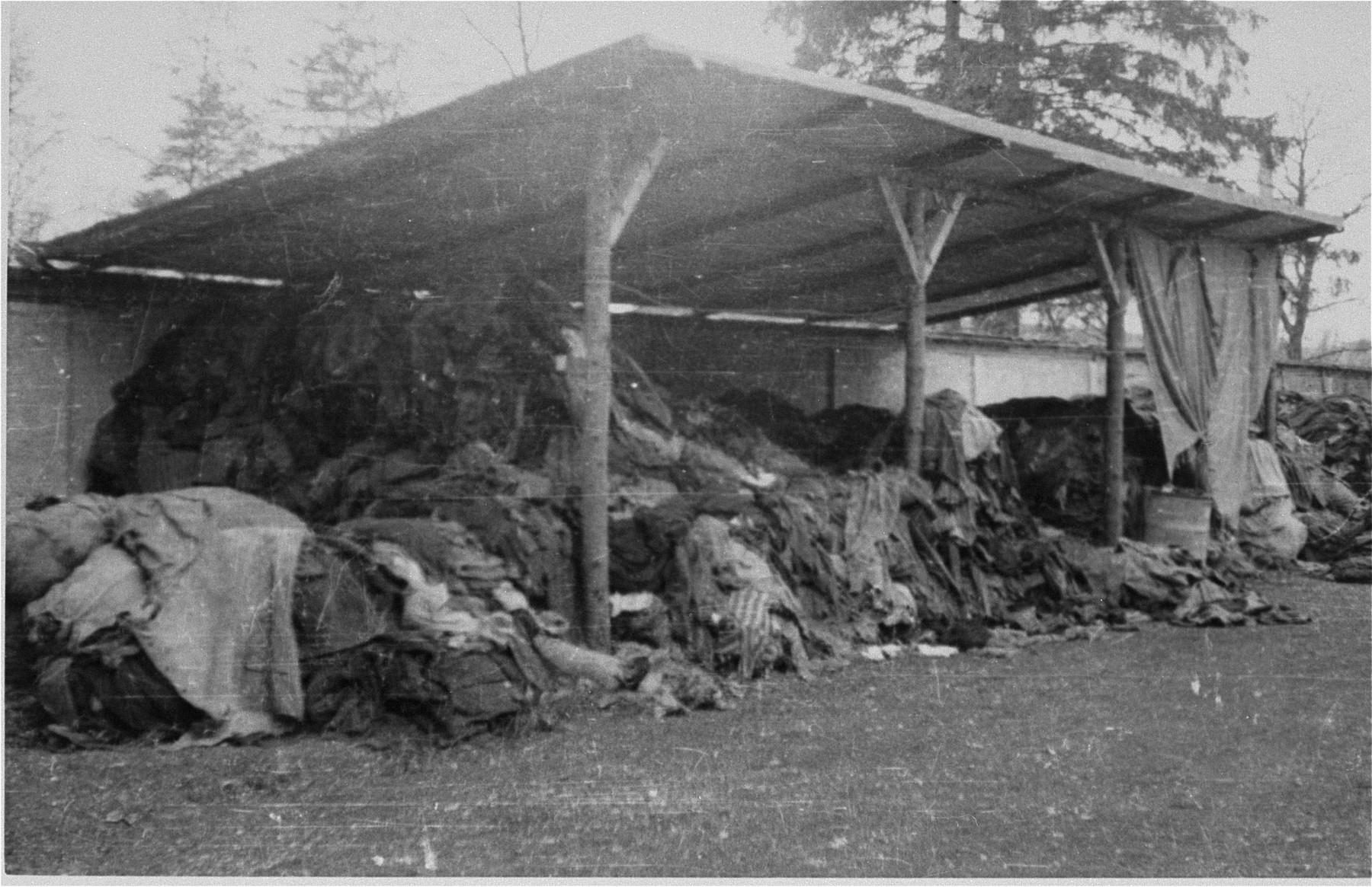 Prisoners clothing piled outside under an overhang.