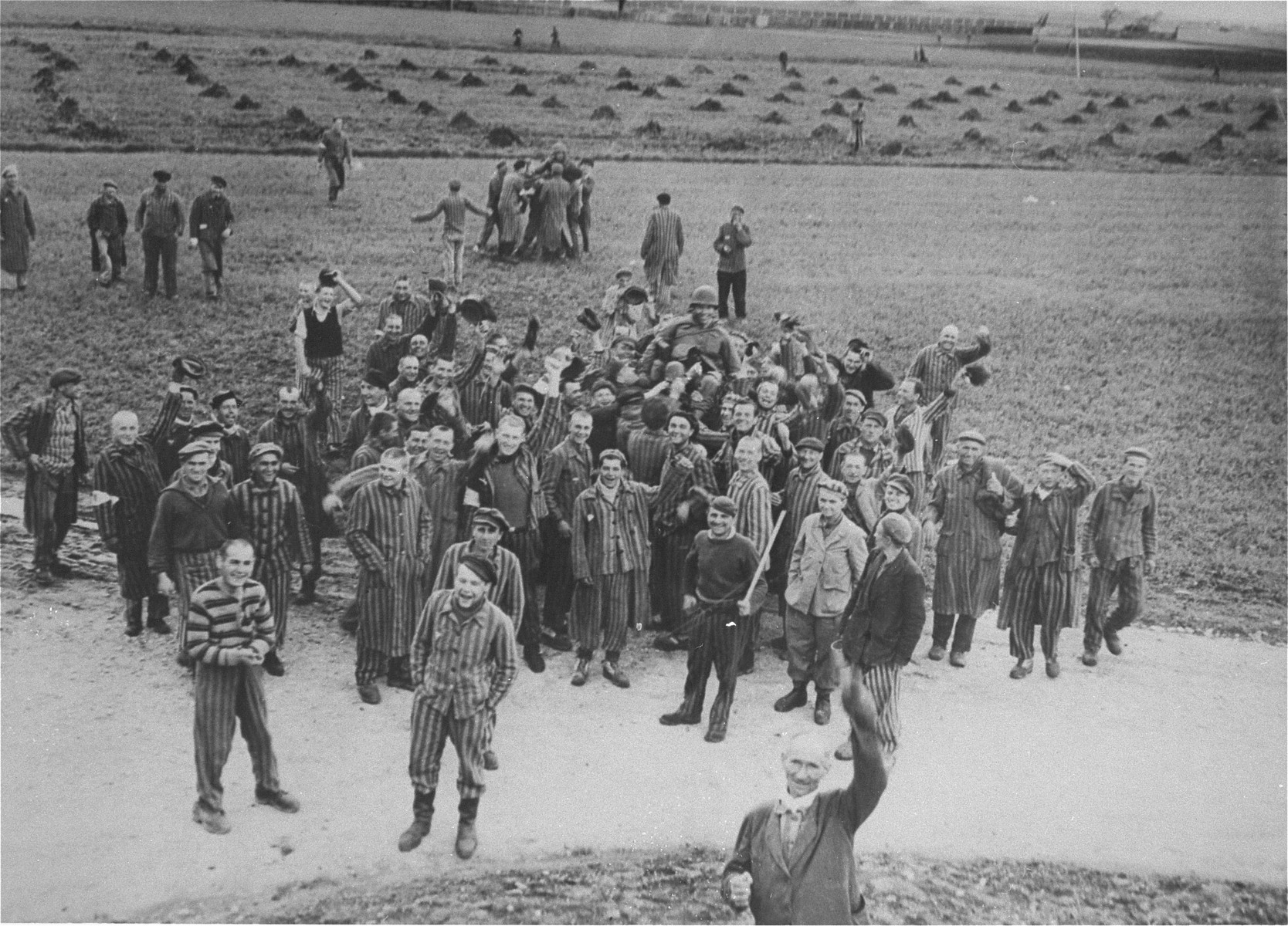 """Survivors in Dachau cheer the arrival of U.S. troops.  Original caption reads: """"Dachau Concentration Camp.  Horrors worse than those found in the German concentration camps of Buchenwald and Belsen were discovered in the stinking hell-hole of Dachau, captured by troops of the 42nd and 45th Infantry Divisions of the Seventh U.S. Army April 30, 1945.  More than 32,000 prisoners were liberated, among them some Englishmen, Canadians and Americans.  The camp was formally surrendered by an SS lieutenant carrying a white flag, accompanied by a Swiss Red Cross official, but SS troops opened fire as American troops approached the main entrance.  The Germans were shot down.  Three prisoners were electrocuted when they tried to burst through the electrified wire barrier to welcome the Americans.  SS guards opened fire on other prisoners who went wild with joy and rushed to meet the liberating troops.  Prisoners with access to records said 9,000 people died of hunger, disease or shooting within the past three months at Dachau.  Four thousand more perished during cold Winter months.  When Americans entered the camp, they found 50 open railway cars standing on a siding, apparently full of dirty clothing but actually found to contain hundreds of corpses piled on top of each other.  They also found a row of kennels where fierce dogs were kept to set after escaping men.  They discovered gas extermination chambers, incinerators full of naked bodies, bodies marked for dissection and the bodies of several small children.    This photo shows: Prisoners of many nationalities show their happiness at being liberated by the Americans by tossing Lieutenant Leonard Zankel of Pittsbugh, Pennsylvania, in the air.  U.S. Signal Corps Photo."""""""