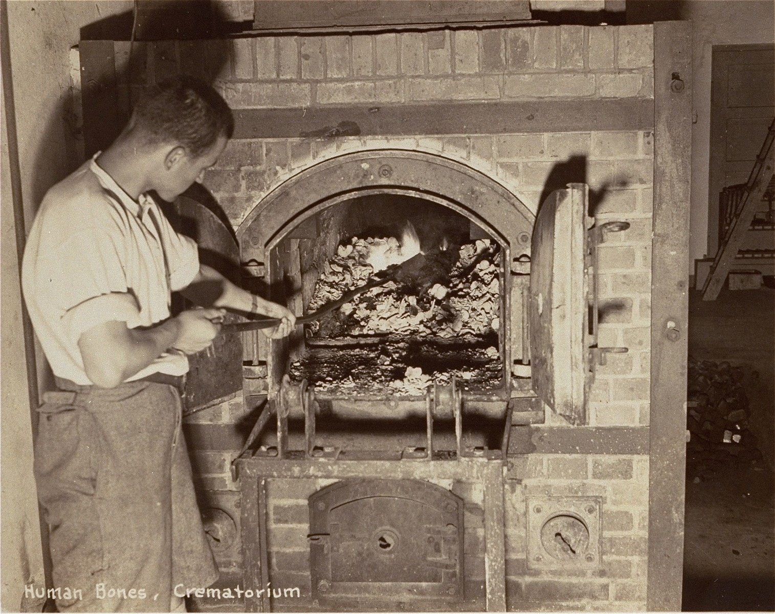 A survivor stokes smoldering human remains in a crematorium oven that is still lit.