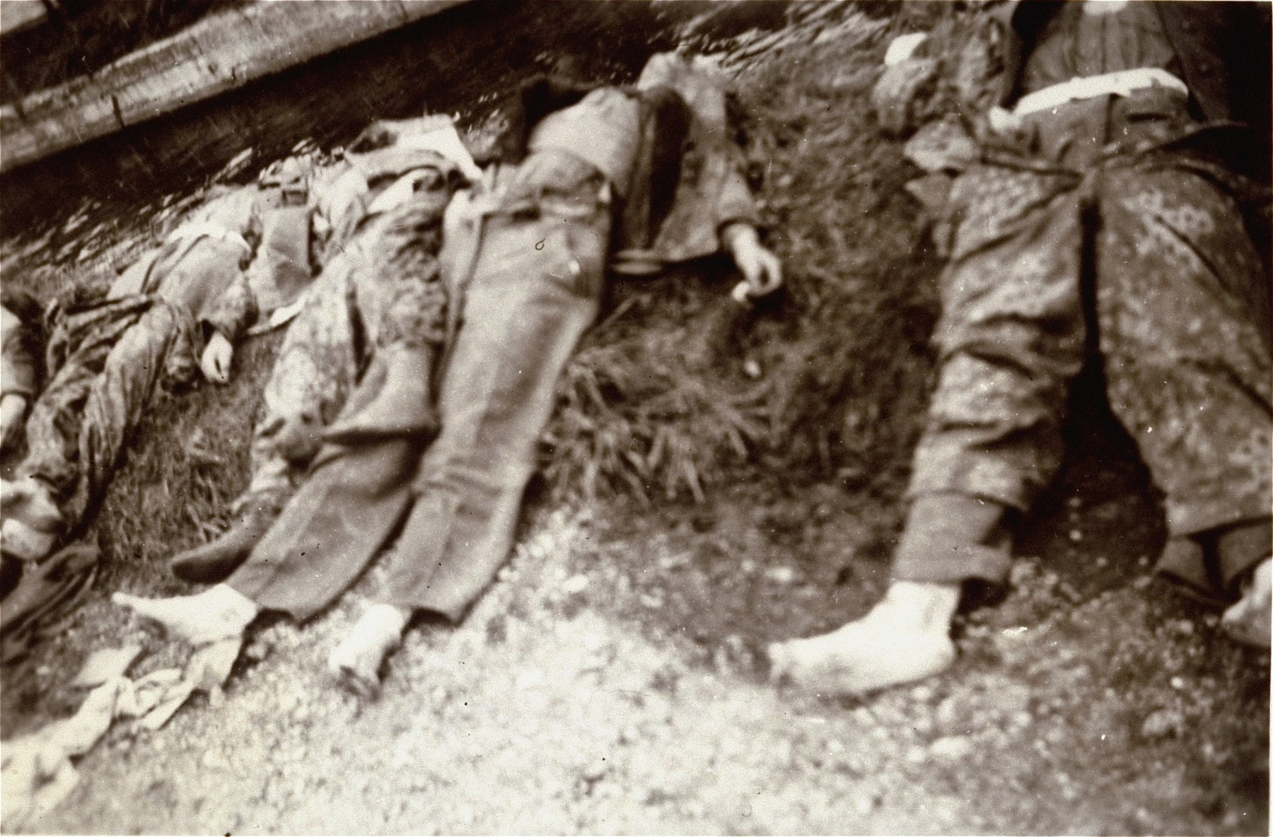 The corpses of SS guards in Dachau lying next to the moat.  Most have been stripped of their boots by survivors.