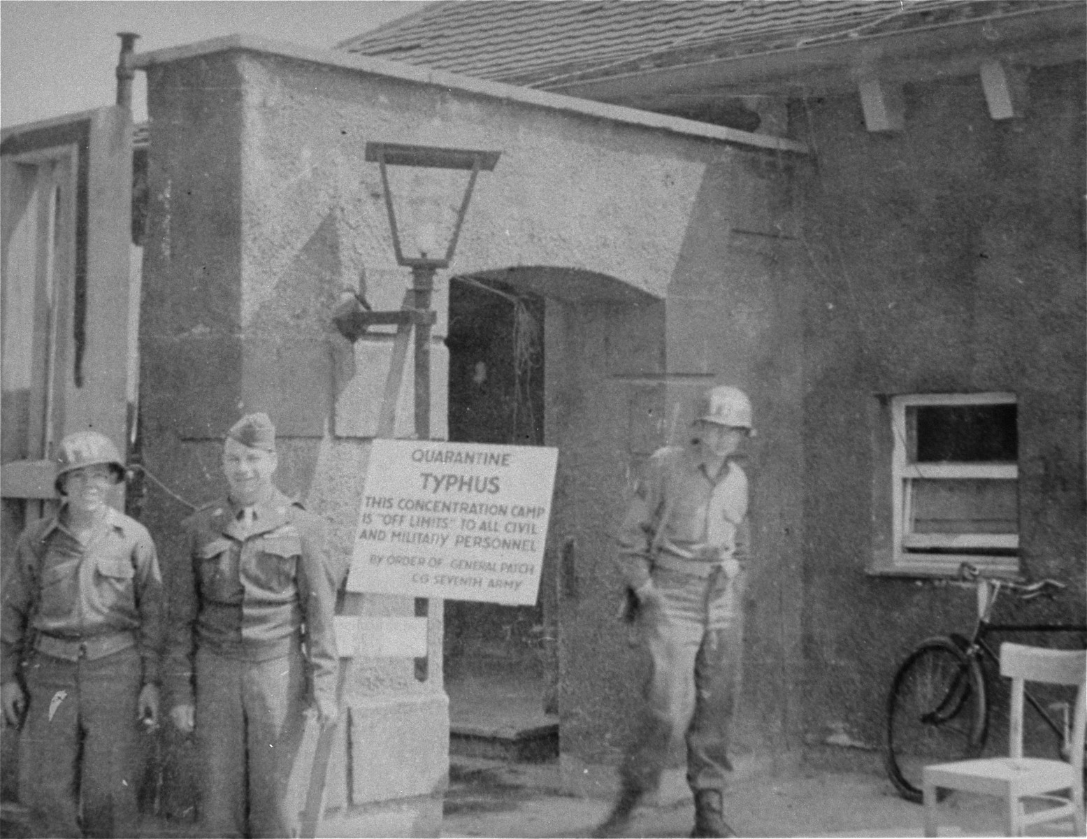 "American soldiers in the Dachau concentration camp.  The sign on the gate reads: ""Quarantine, Typhus, This Concentration Camp is Off Limits to all Civil and Military Personnel.  By Order of General Patch, CG Seventh Army""."