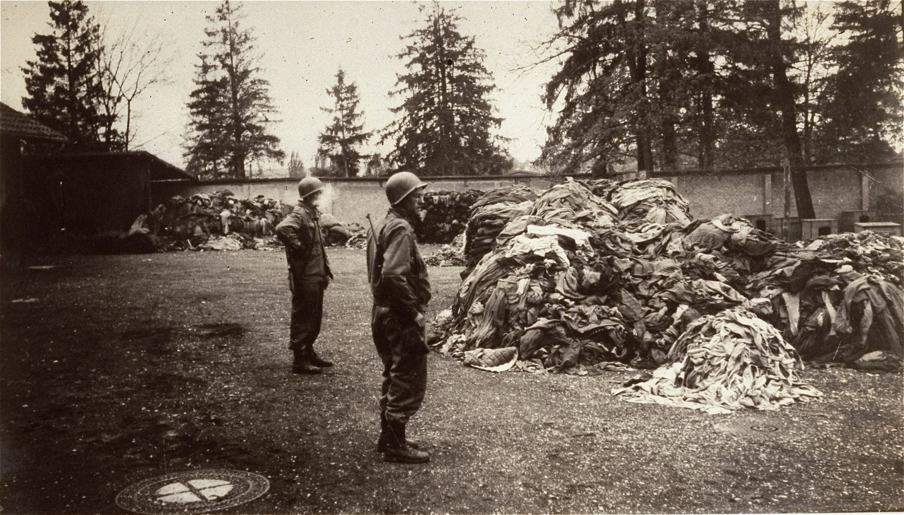 American soldiers in Dachau examine piles of prisoners' clothing found near the crematorium.
