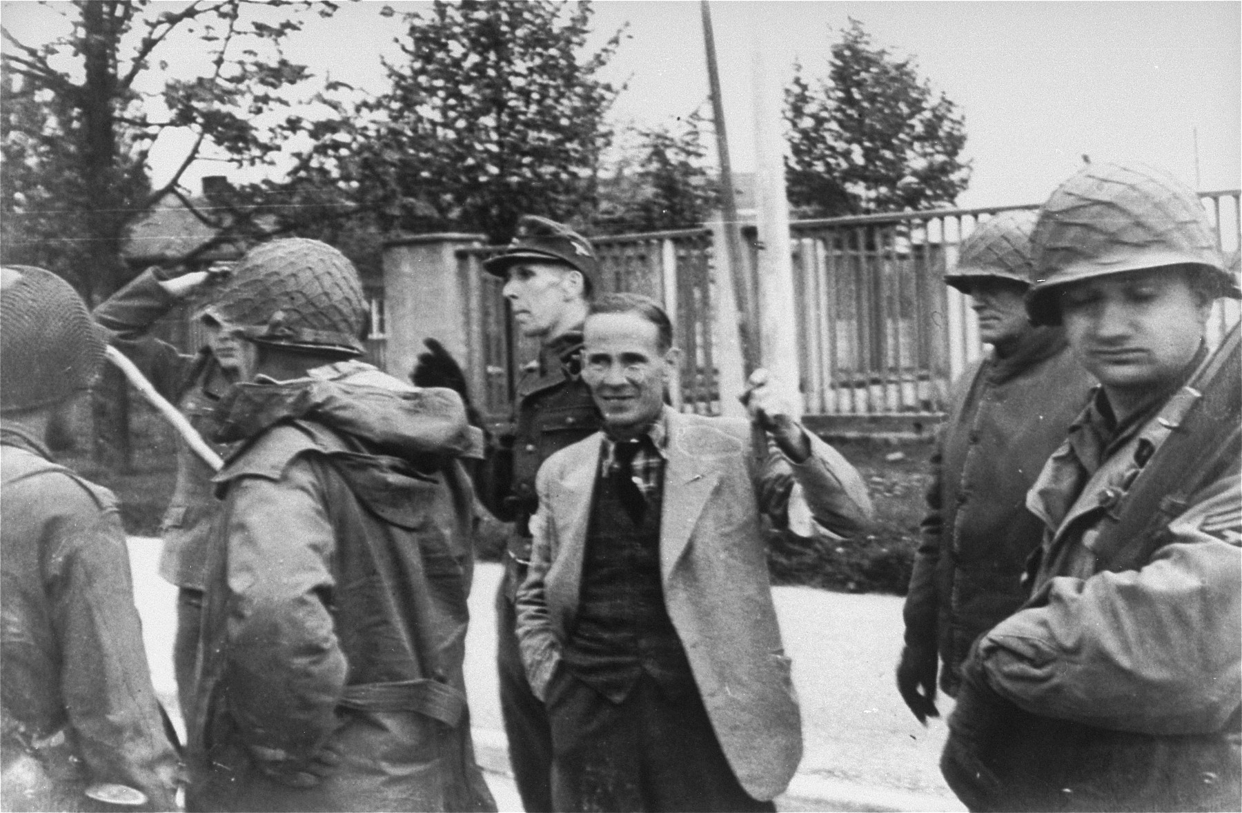 Brigadier General Henning Linden, assistant commanding general, 42nd Rainbow Infantry division, with his back to the camera, accepting the surrender of SS Lt. Wickert.  The man in the middle is ICRC (International Committee of the Red Cross) representative Dr. Vincent  Maurer, acting as a translator for the surrendering Germans. [oversized print]