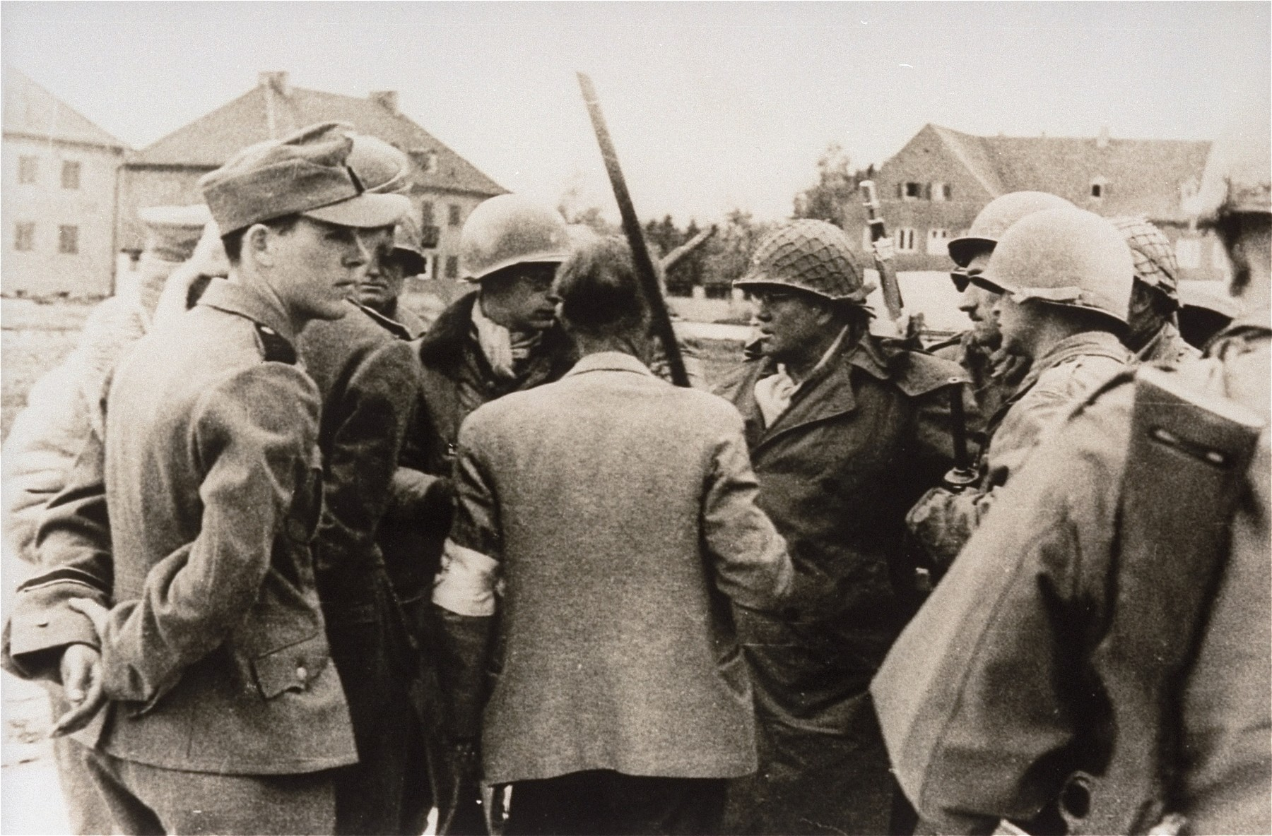 General Henning Linden, assistant commanding general, 42nd Rainbow Infantry Division, confers with various officials during the liberation and surrender of the Dachau concentration camp.   Pictured from left to right are: an aide to SS Lt. Wickert, who surrendered the camp; Lt. Wickert (partially hidden by his aide); Paul M.G. Levy, a Belgian journalist attached to SHAEF, who is serving as an interpreter; Dr. Victor Maurer (back to the camera), the delegate of the International Red Cross, who arranged the terms of the surrender; General Henning Linden; Linden's bodyguards.  Maurer is holding a makeshift flag of surrender constructed from a broomstick; [oversize print]