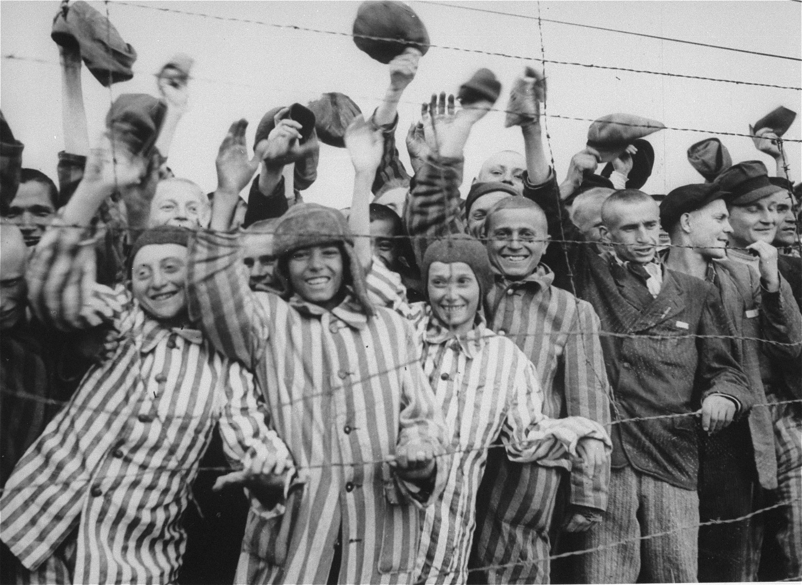 "Survivors cheer the arrival of American liberators.    Among those pictured are Juda Kukieda (middle), to his right is Szmulek Rozental (now Steve Ross),  David Moszkowicz (third from the left) and Gyorgy Laszlo Spiegel (far left).  Original caption reads: ""Dachau Concentration Camp.  Horrors worse than those found in the German concentration camps of Buchenwald and Belsen were discovered in the stinking hell-hole of Dachau, captured by troops of the 42nd and 45th Infantry Divisions of the Seventh U.S. Army April 30, 1945.  More than 32,000 prisoners were liberated, among them some Englishmen, Canadians and Americans.  The camp was formally surrendered by an SS lieutenant carrying a white flag, accompanied by a Swiss Red Cross official, but SS troops opened fire as American troops approached the main entrance.  The Germans were shot down.  Three prisoners were electrocuted when they tried to burst through the electrified wire barrier to welcome the Americans.  SS guards opened fire on other prisoners who went wild with joy and rushed to meet the liberating troops.  Prisoners with access to records said 9,000 people died of hunger, disease or shooting within the past three months at Dachau.  Four thousand more perished during cold Winter months.  When Americans entered the camp, they found 50 open railway cars standing on a siding, apparently full of dirty clothing but actually found to contain hundreds of corpses piled on top of each other.  They also found a row of kennels where fierce dogs were kept to set after escaping men.  They discovered gas extermination chambers, incinerators full of naked bodies, bodies marked for dissection and the bodies of several small children.    This photo shows: Former prisoners of the Nazis, some wearing the characteristic striped dress of the concentration camp, wildly cheer troops of the Seventh U.S. Army following their liberation from the horrors of Dachau."""