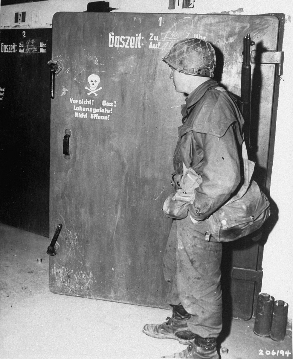 "A soldier from the U.S. 7th Army examines the door to a gas chamber in the Dachau concentration camp.  Original caption reads,  ""Gas chambers, conveniently located near the crematory, are examined by a U.S. Army solider.  These chambers were a part of the annihilation system at Dachau."""