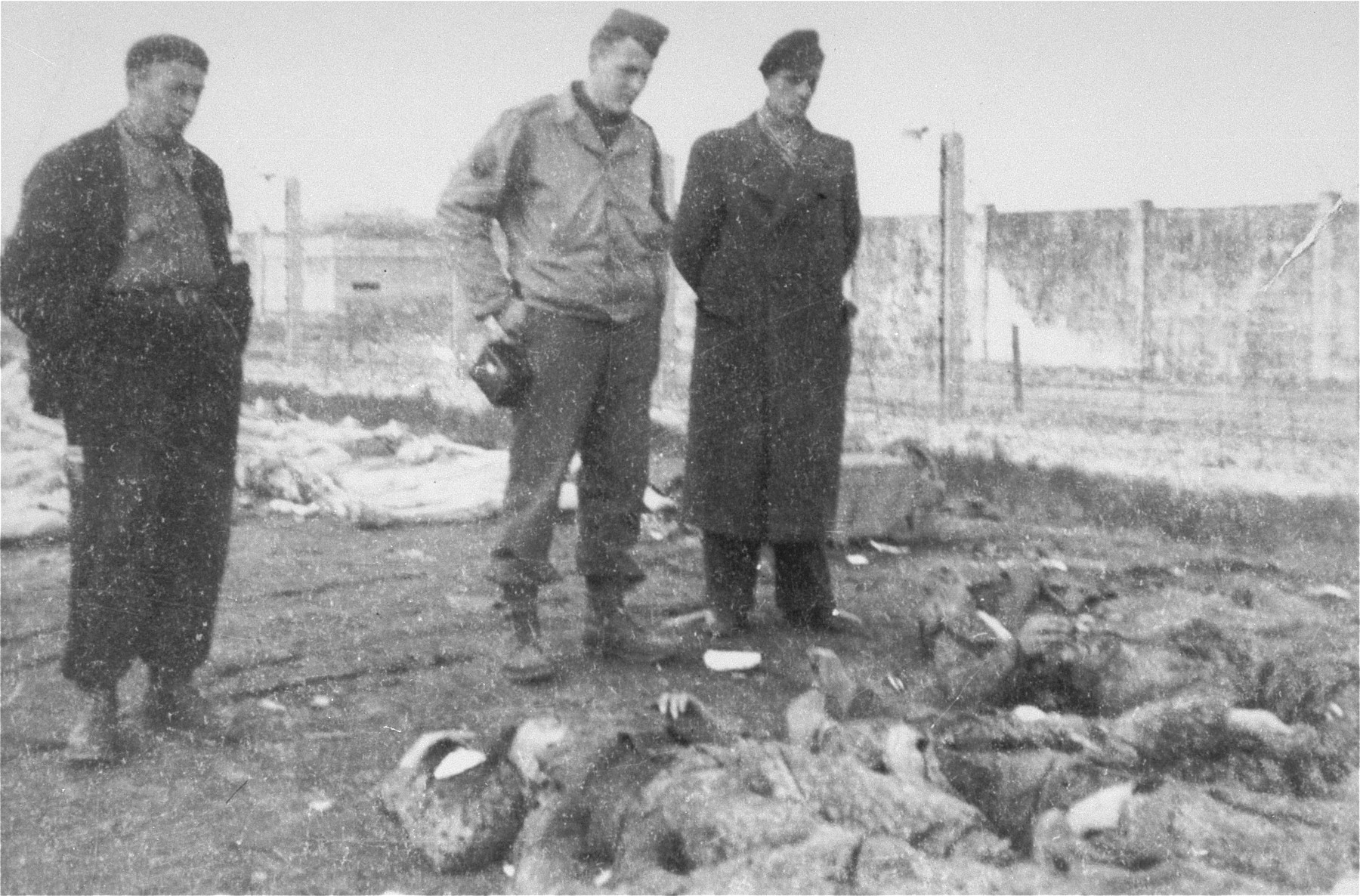 An American soldier and two survivors examine the bodies of SS guards killed by U.S. troops during the liberation of the camp.