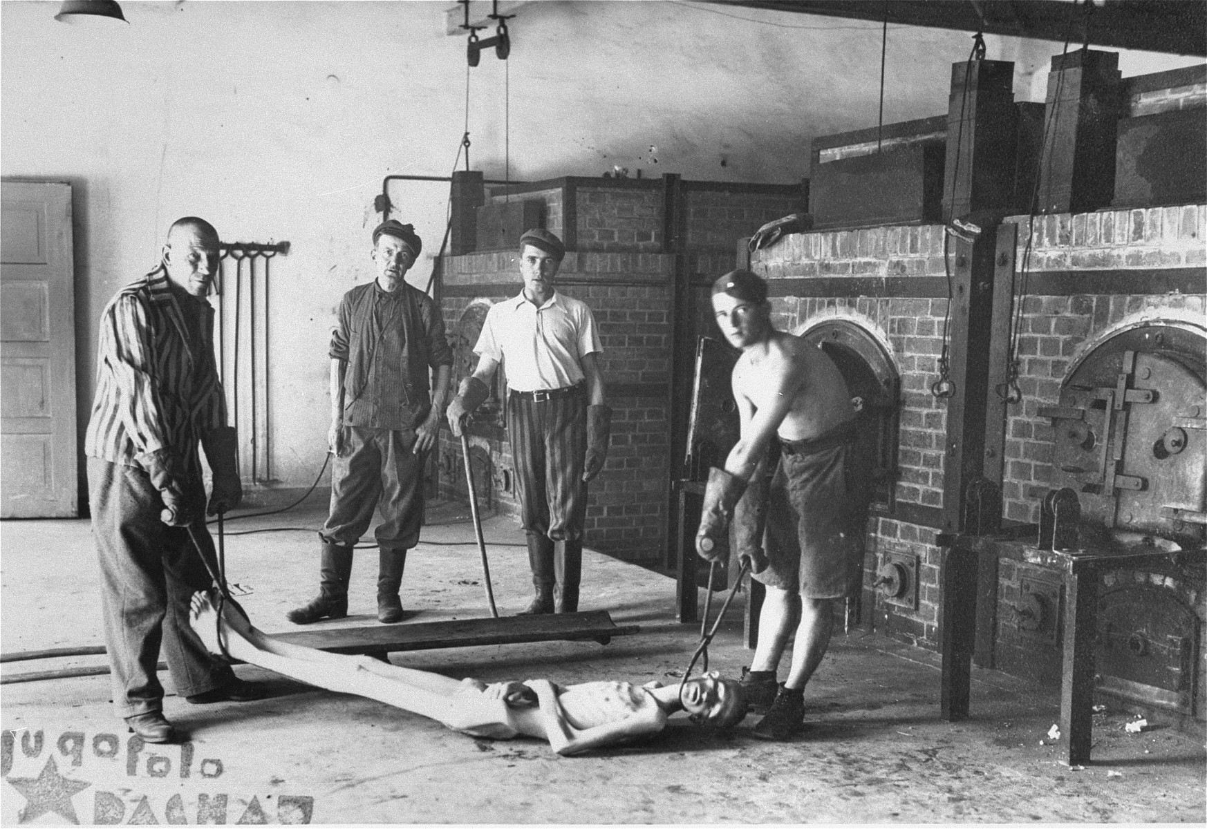 Survivors of the Dachau concentration camp demonstrate the operation of the crematorium by preparing a corpse to be placed into one of the ovens.