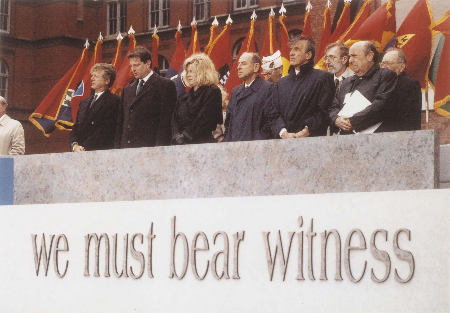 At the dedication ceremony of the opeing of the Museum, participants listen to Bishop Krister Stendahl's invocation as liberation unit flags snap in the wind.   Pictured from left to right are: Ted Koppel, Albert Gore, Tipper Gore, Harvey Meyerhoff, Elie Wiesel, James Ingo Freed, unidentified and Jeshajahu Weinberg.