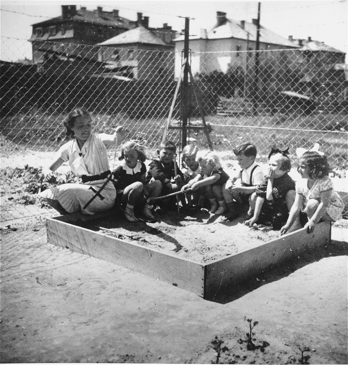 A group of Jewish and Hungarian children play with their teacher in a sandbox in the playground of a pre-school in Budapest.    The pre-school was located on Tokoly Street in the 14th district.  Gyorgy Pick is seated third from the right.