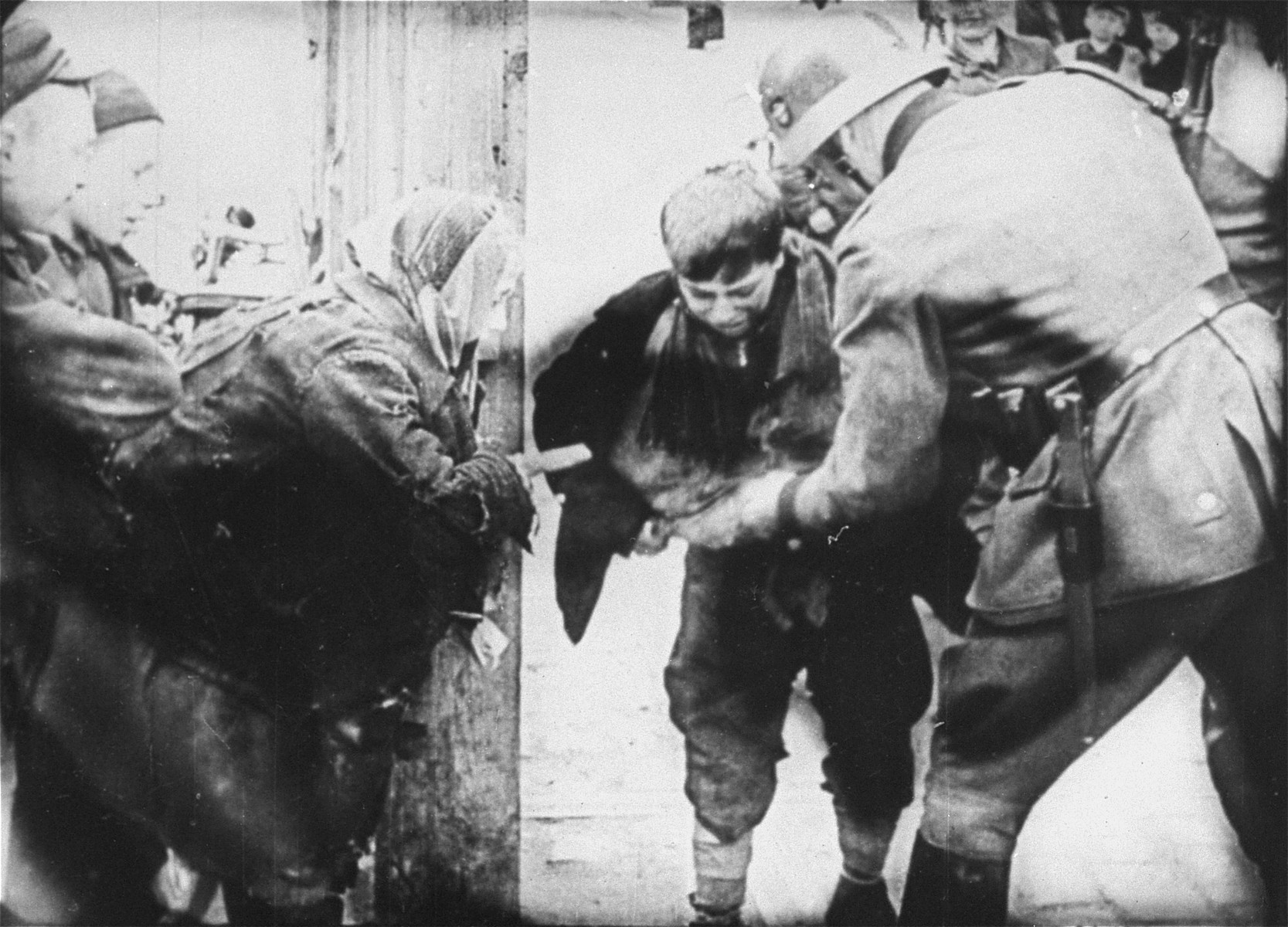 A young boy caught smuggling in the Warsaw ghetto by a German policeman.