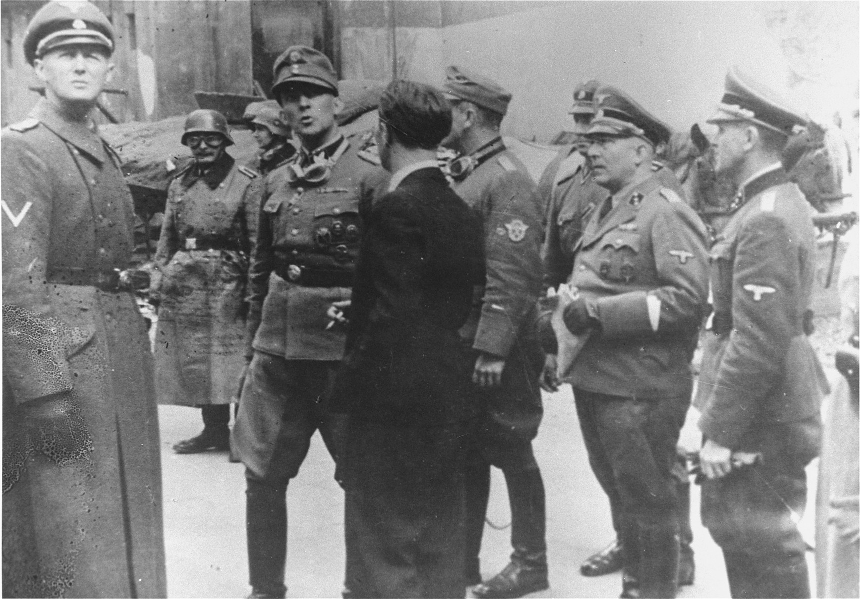 SS Major General Juergen Stroop (second from left) gathers information from a civilian on the second day of the suppression of the Warsaw ghetto uprising.    Accompanying Stroop are the various officers of his command staff, including SS Fuehrer Conrad (left), Stroop's police adjutant, Kaleschke (partially hidden), SS Lieutenant (Untersturmfuehrer) Karl Brandt (third from right), SS Lieutenant (Untersturmfuehrer) Schwarz (second from right), and a lieutenant (Untersturmfuehrer) in the SD.