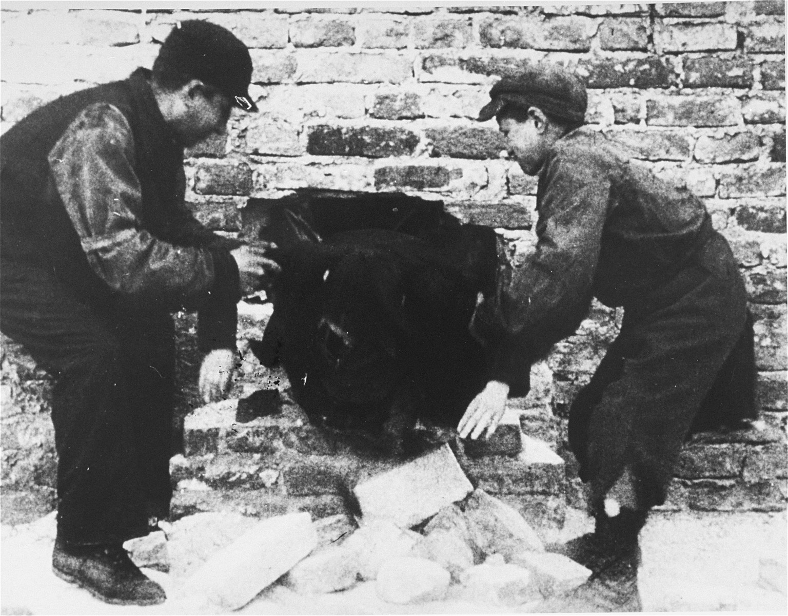 Two young smugglers pull a third through a hole in the ghetto wall.