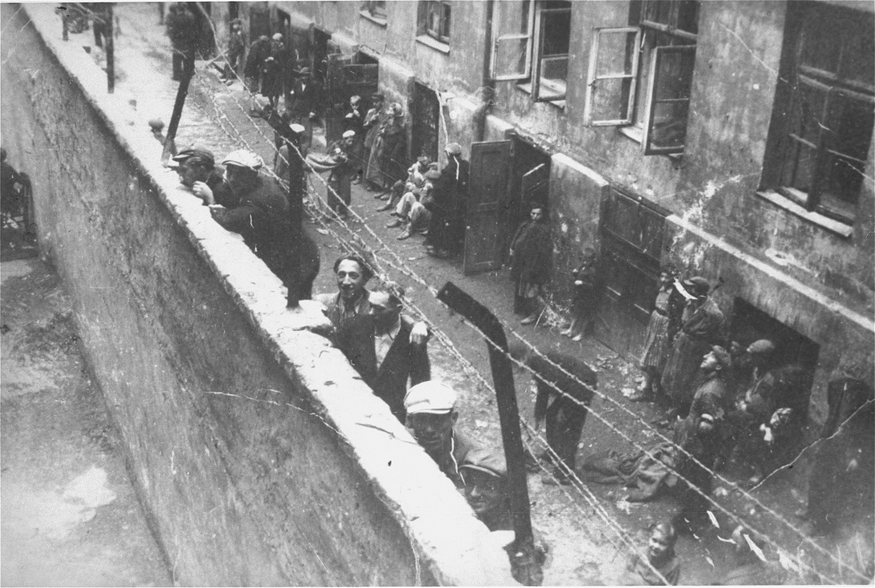 "Jewish youth peer over the wall overlooking Mirowski Plac (Square) that divided the Warsaw ghetto into the small and large ghettos.    On the ladder at the wall are Ajzyk and Jakob Wierzbicki.  The apartment house in the background (located at 12 Krochmalna Street) was the home of the donor, Irving Milchberg, and his family until 1942.   Milchberg crossed over to the ""Aryan"" side of Warsaw after the deportation of his family and became involved with a group of Jewish children and youth who supported themselves by selling cigarettes at Three Crosses Square (Plac Trzech Krzyzy). He was known as ""Byczek"" (Bull)."