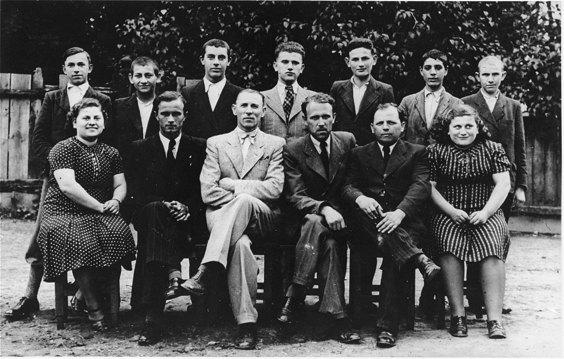 Group portrait of students who are training to be tailors at a vocational school in Tacovo.  Pictured in the front row, from left to right are: Malvina Ickovic; Jonko Jeno (the Hungarian language teacher); Raives (the director of the school); unknown; Mendel Rezmovics (a teacher); and Sheindy Ickovic.  In the back row, from left to right are: Horbas; Tobias; Stal; Ludvic Ickovic; Lajbl Fixler; Cali Kaufman and Moshe Joel Smajovics.