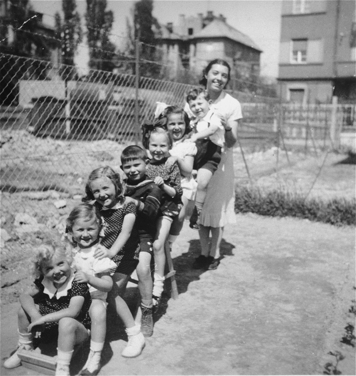 A group of Jewish and Hungarian children pose with their teacher on a seesaw in the playground of a pre-school in Budapest.    The pre-school was located on Tokoly Street in the 14th district.  Gyorgy Pick is seated closest to the teacher.