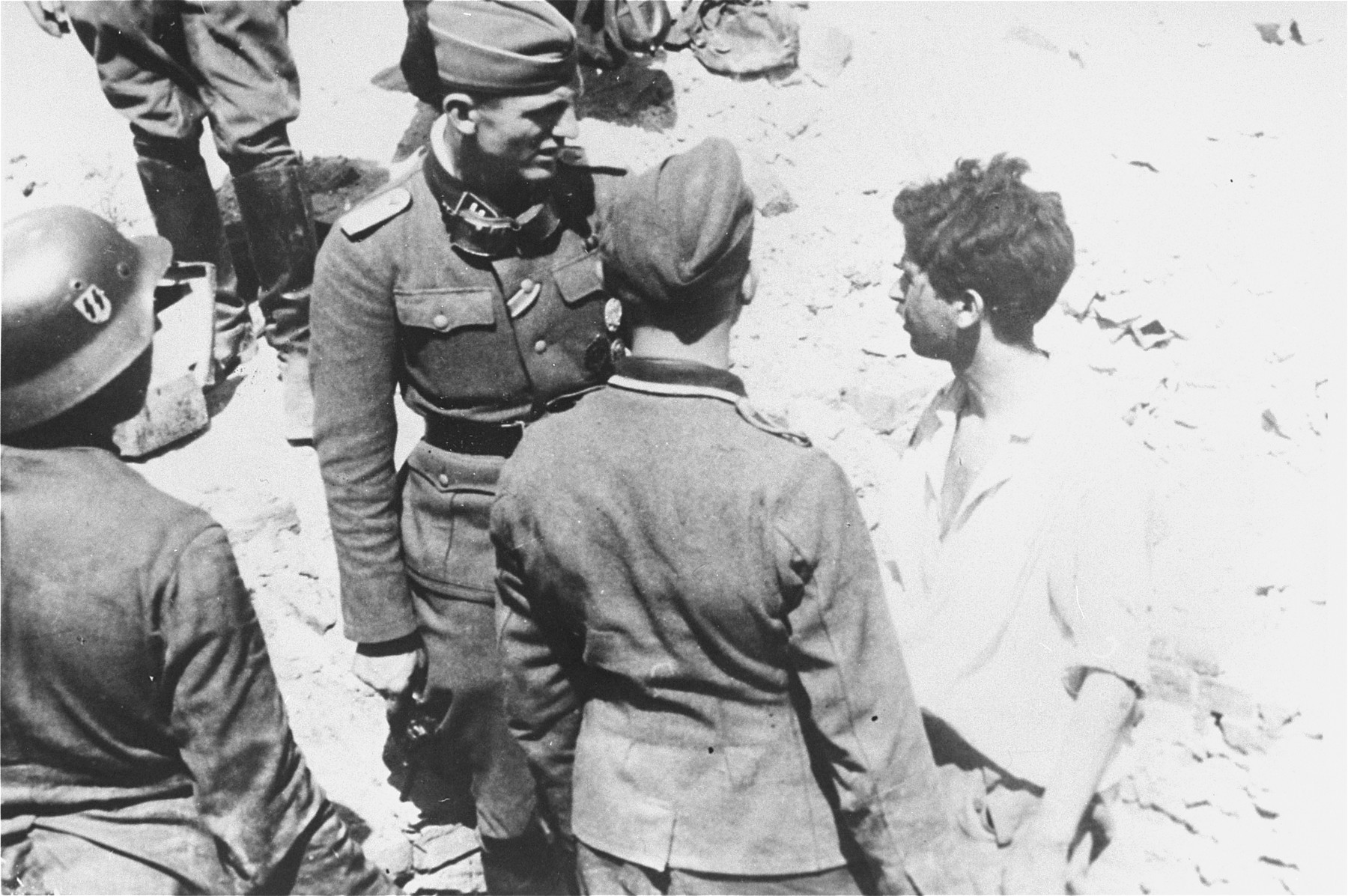 An SS Lieutenant (Untersturmfuehrer) interrogates a Jewish resistance fighter captured on the twenty-first day of the suppression of the Warsaw ghetto uprising.