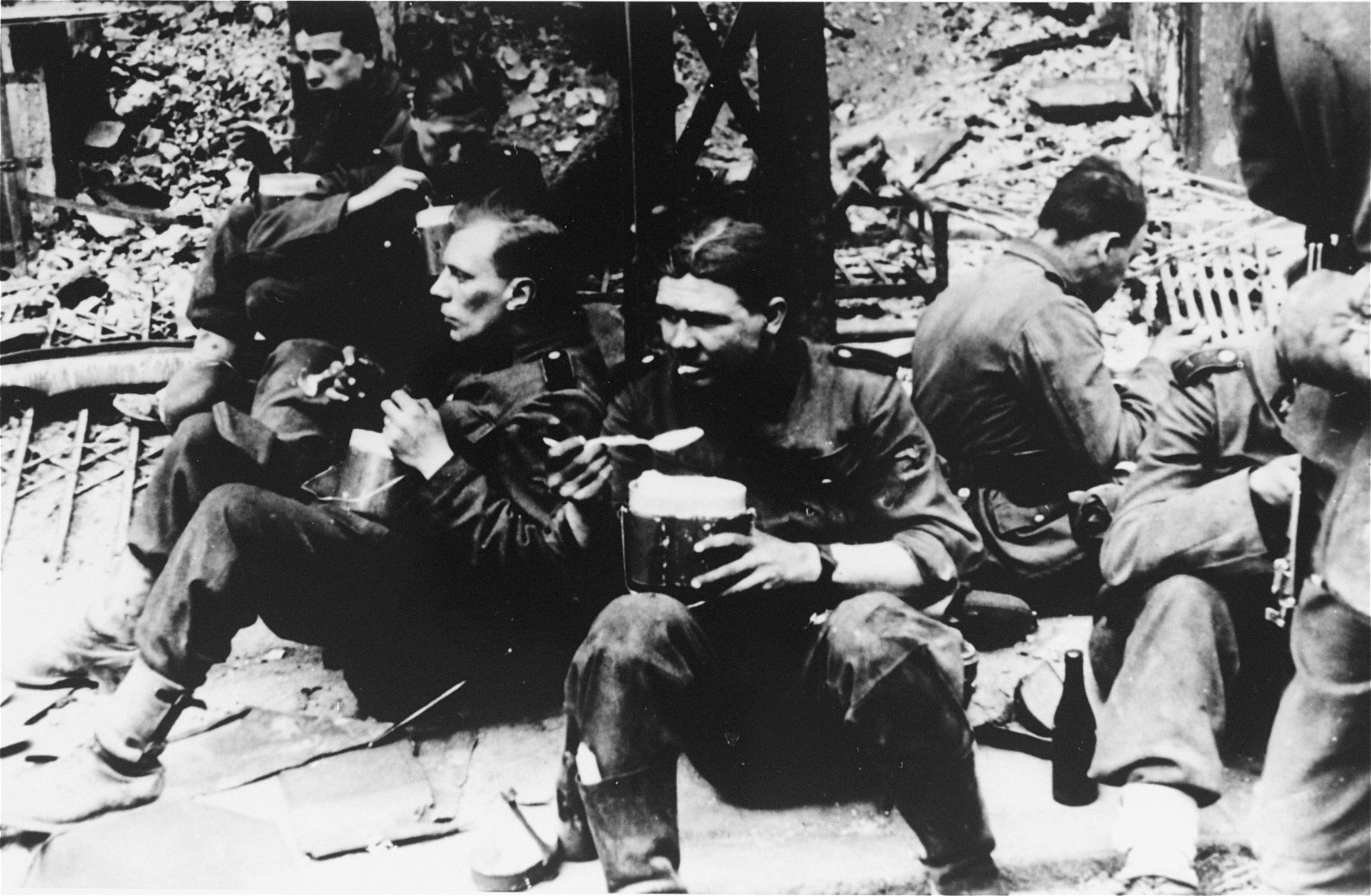 SS soldiers pause to eat during the suppression of the Warsaw ghetto uprising.