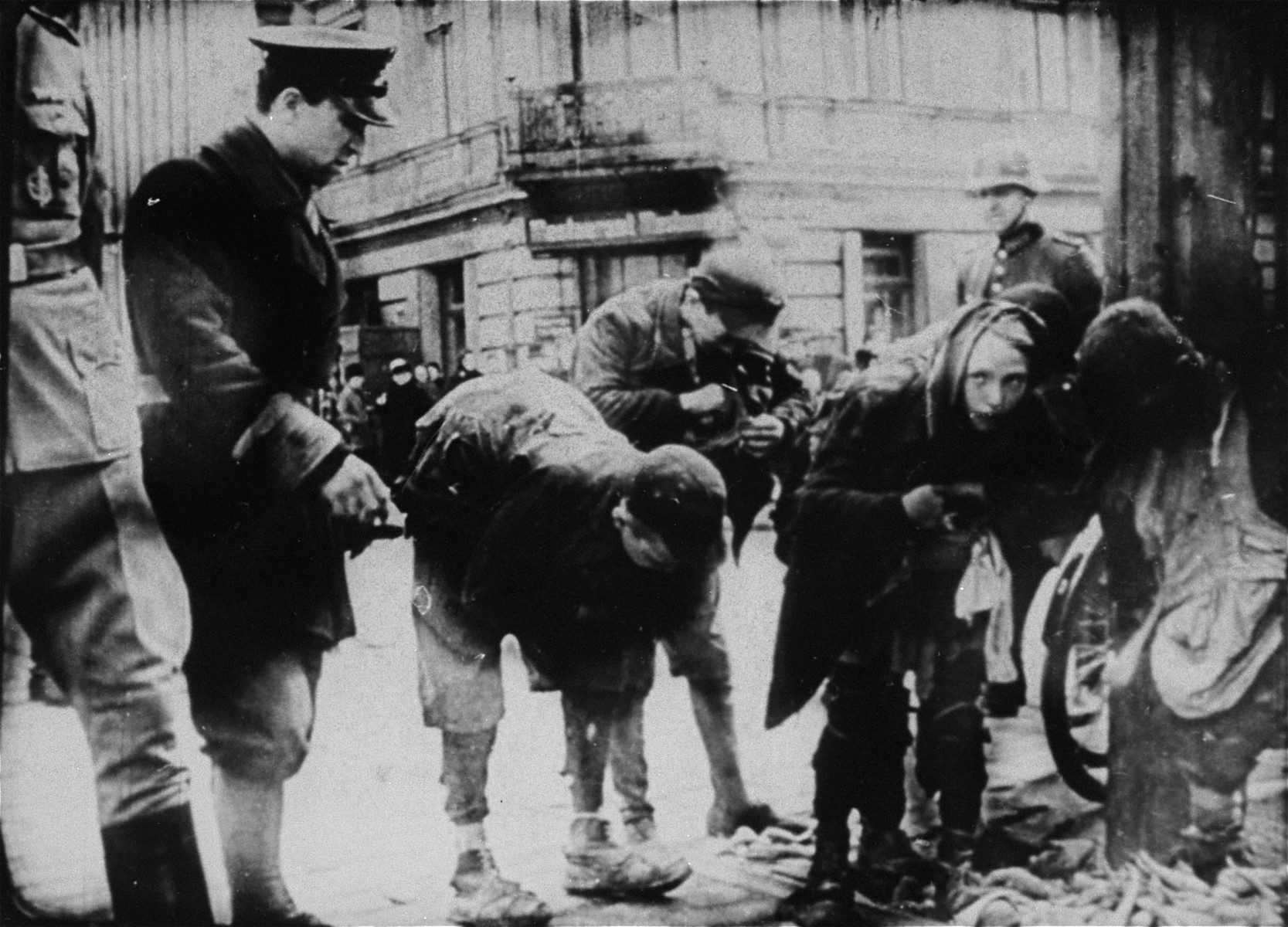 Young boys caught smuggling by a German soldier in the Warsaw Ghetto.