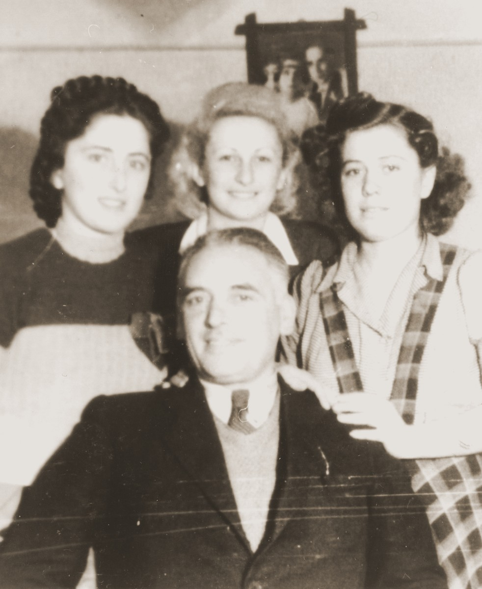 Group portrait of four Jews in an apartment in the Cernauti ghetto.  Pictured standing from left to right are Erika and Beatrice Neuman and an unidentified woman; seated is Dr. Heller.