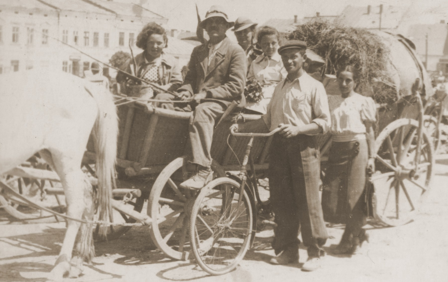 A Jewish family moves their belongings by horse-drawn wagon into Lancut, Poland.  Pictured from left to right are: Basia, Sara, and Ita Gurfein.  Standing is Feiga Gerstein (Sara Gurfein Gerstein's sister-in-law).