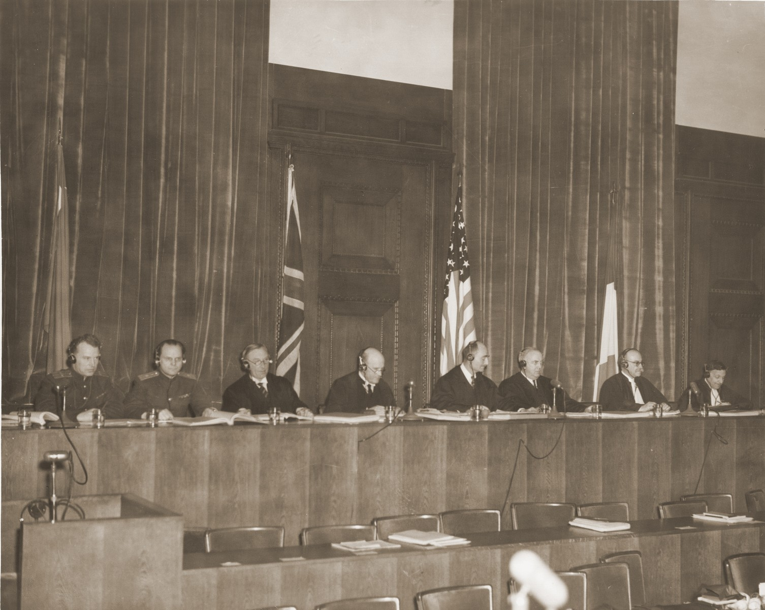 View of the judges' bench at the International Military Tribunal in Nuremberg.    Pictured from left to right are:  Lt. Col. A.F. Volchkov and Maj. Gen. Nikitchenko (USSR); Justice Norman Birkett and Tribunal President Lord Justice Geoffrey Lawrence (Great Britain); Judge Francis Biddle and Judge John J. Parker (U.S.); Prof. Donnedieu de Vabres and Robert Falco (France).