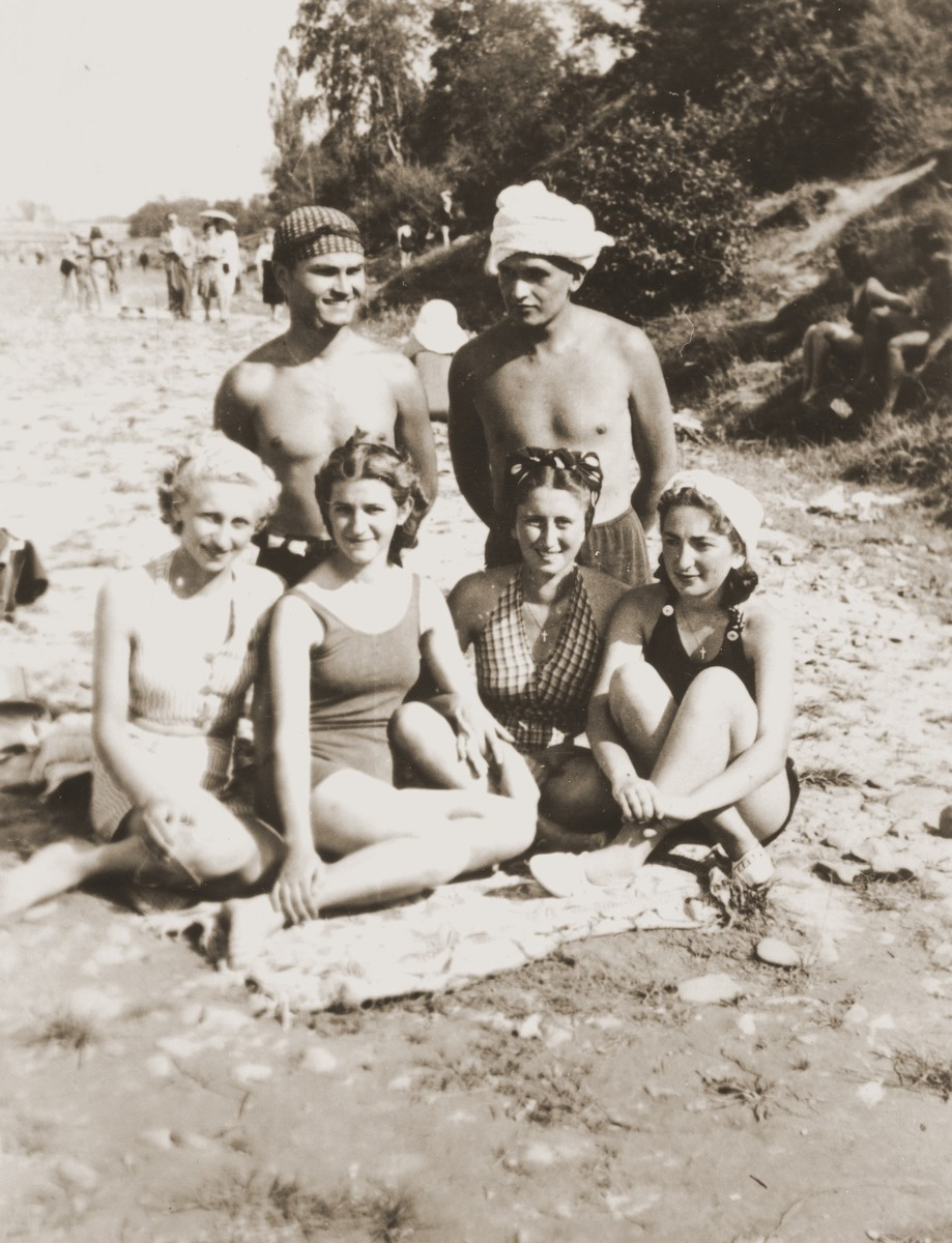 Three Jewish girls in hiding relax on a beach with a Romanian girlfriend.  Pictured are Beatrice and Erika Neuman, and Cila Loewenthal.  After having received false papers, the girls put on crosses and snuck out of the ghetto.  The two boys are Romanians whom they met that day.