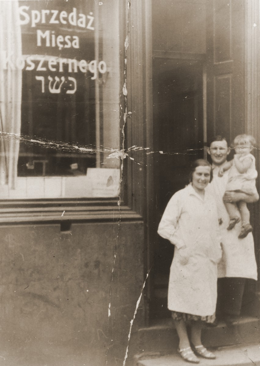 Izak and Tola Goldblum pose with their daughter Salusia in the doorway of their kosher butcher shop in Katowice.