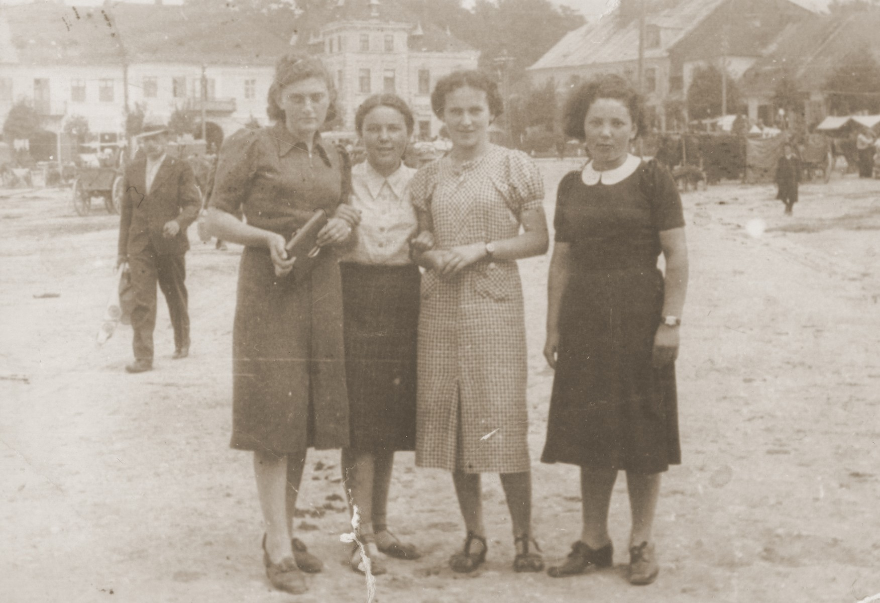 Group portrait of four young Jewish women in a public square in Lancut, Poland.  Pictured from left to right are: Ethel Ringelheim, Sheila Gurfein, Esther Amet and Basia Gurfein.