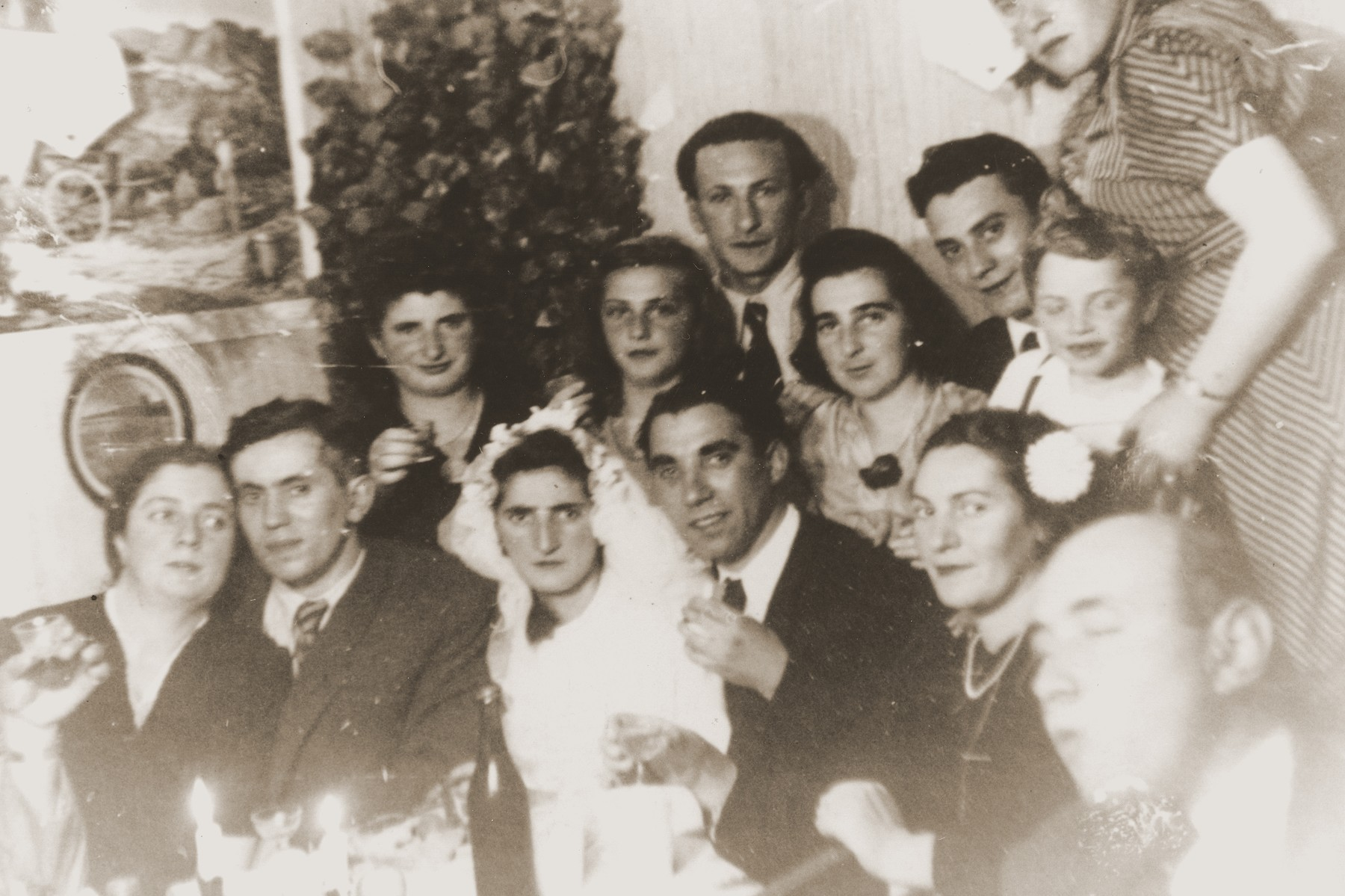 Friends and family pose with the bride and groom at a wedding celebration in the Bergen-Belsen displaced persons camp.  Pictured are the bride and groom Manya (Goldblum) and David Marmor