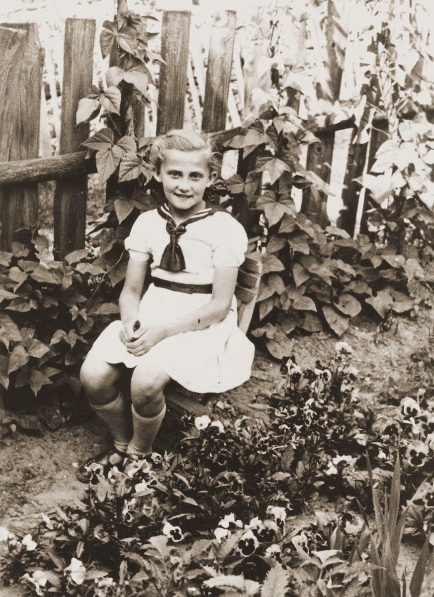 Seven year old Salusia poses in a garden in Zarki, where she was sent in the company of a Polish woman to check on the whereabouts of her grandparents.