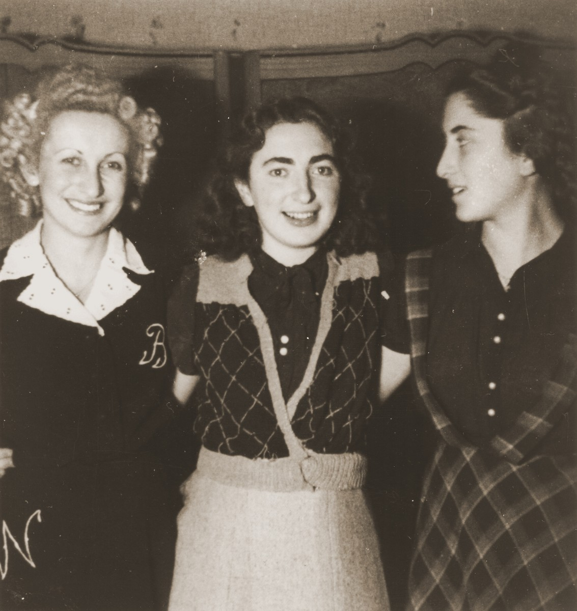 Three young women pose in the Cernauti ghetto.  Pictured from left to right are Beatrice Neuman, Erika Neuman and their friend Cila Loewenthal.