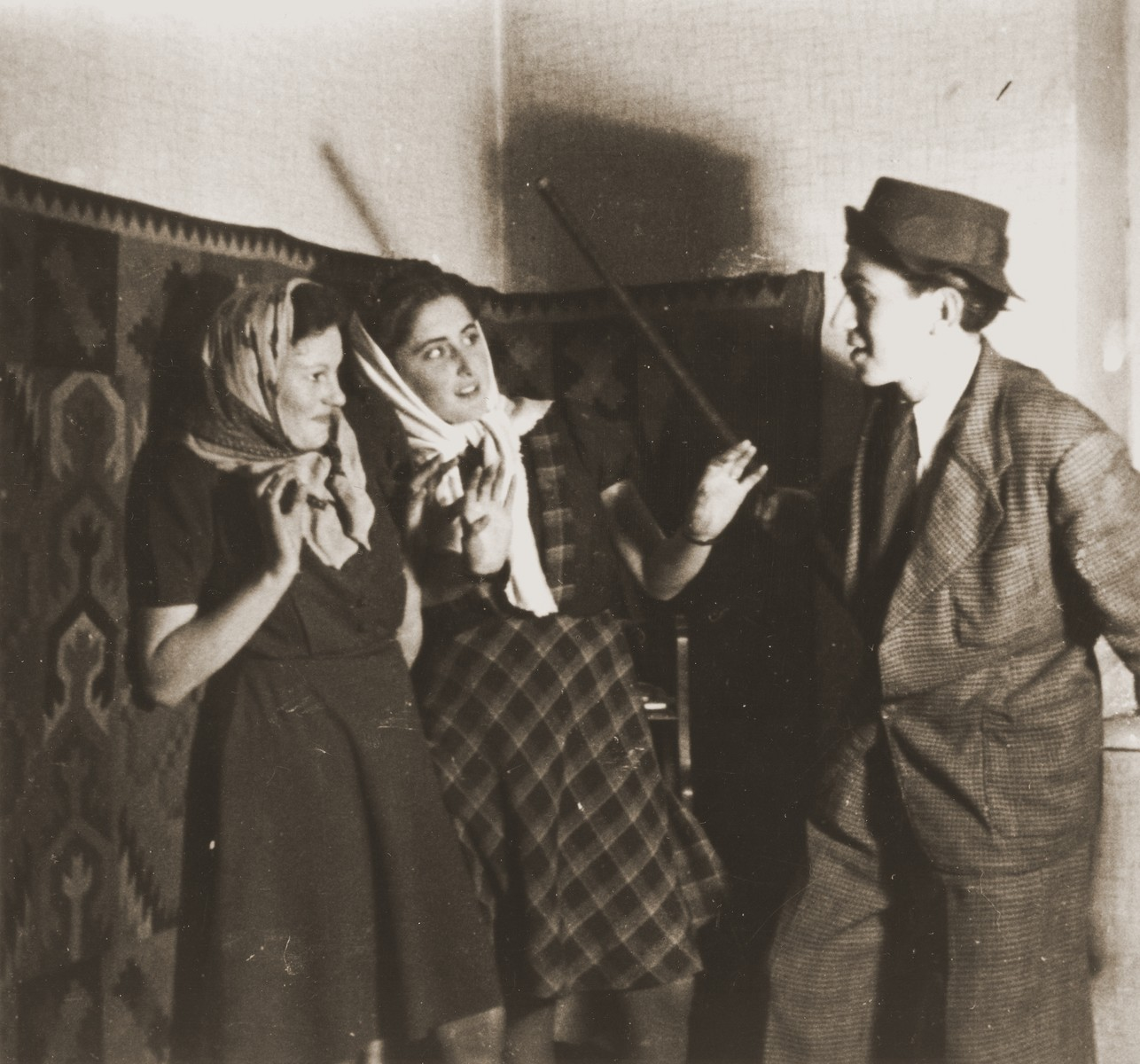 Three young Jews act in a play in the Cernauti ghetto.  Among those pictured is Erika Neuman (center).