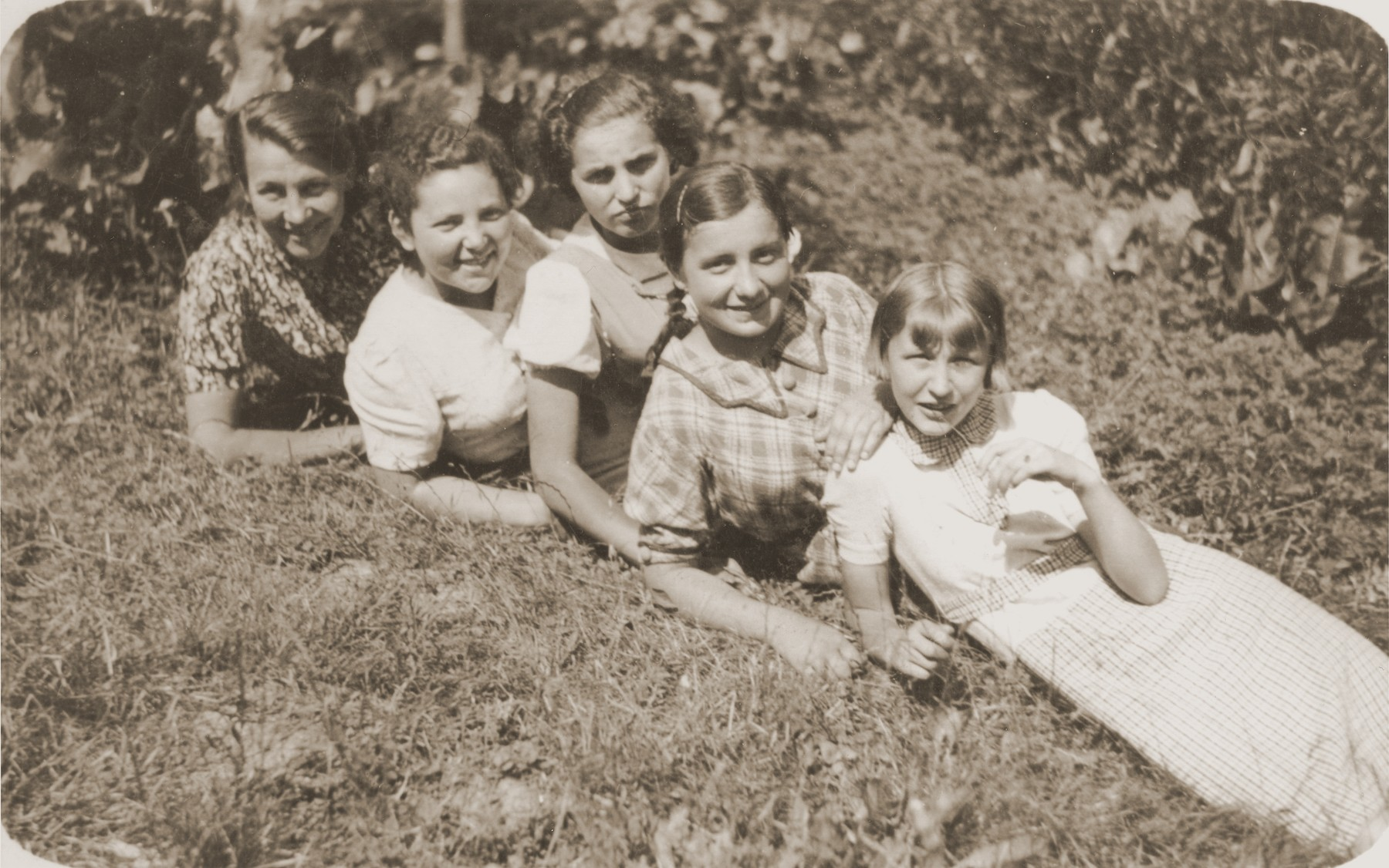 Four girls pose outside in the grass with their sewing teacher.  Among those pictured is Basia Gurfein (second from the left). The teacher is on the far left.