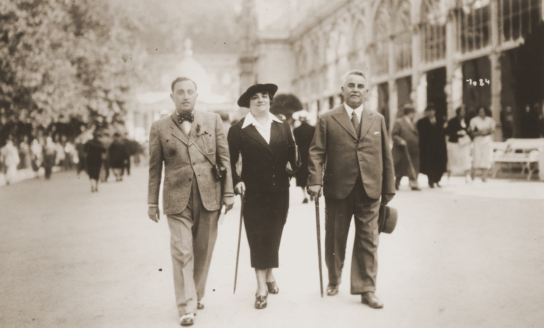 Two men and a woman walk along a street while on vacation in Marienbad, Czechoslovakia.  Julius Reinhold is pictured on the left.