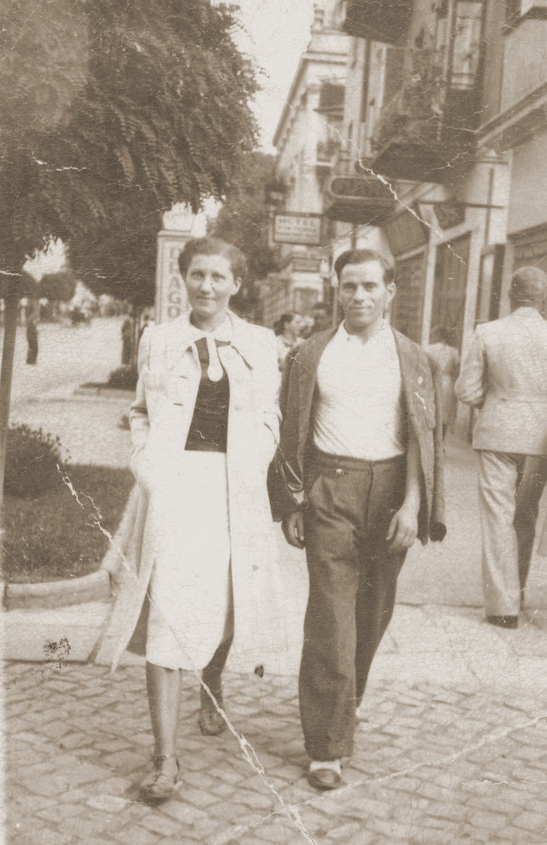 A young Jewish couple walks along a street in Zwolen, Poland.  Pictured are Yoel and Helen Feldberg, the brother and sister-in-law of Sara (Feldberg) Miedzinski.