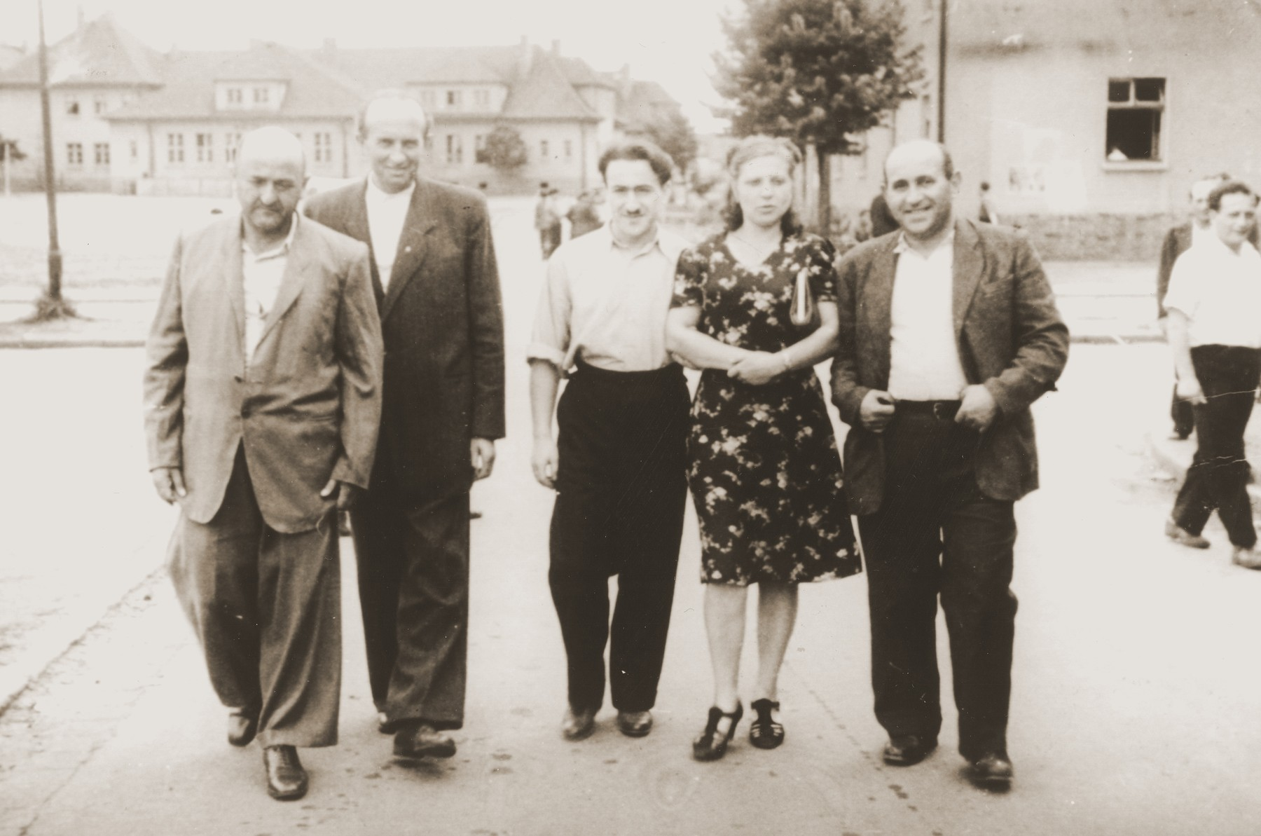 Moishe Broda walks along a street with a group of friends in the Bergen-Belsen displaced persons camp.