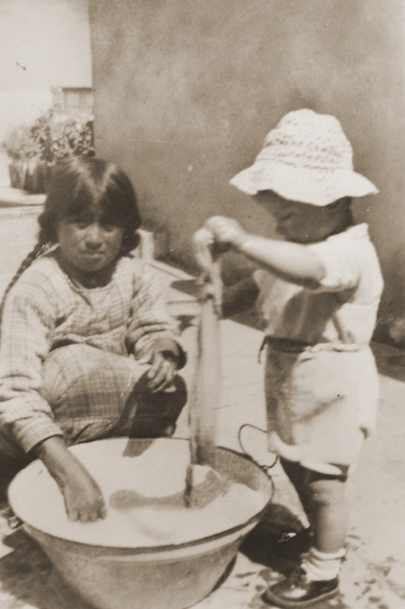 Nineteen-month-old Leo Spitzer and a Bolivian child wash clothes in a basin outside the Spitzer home.