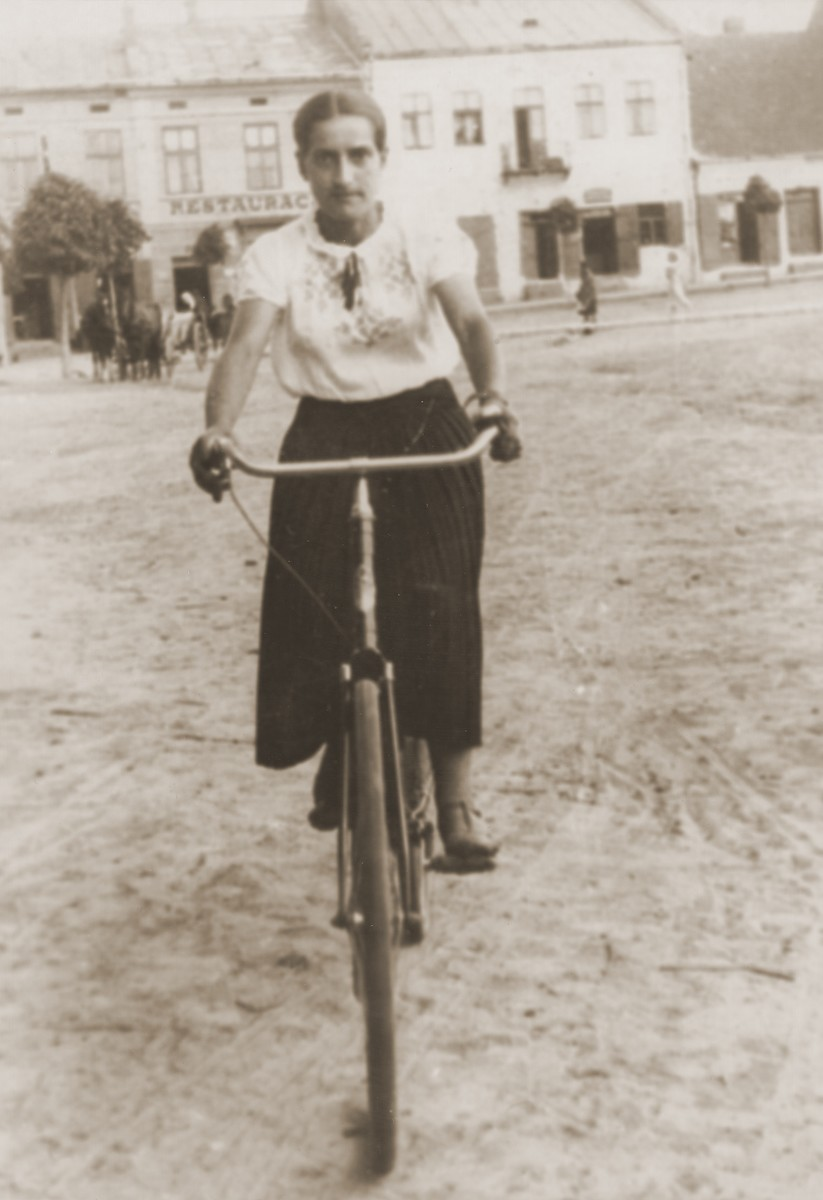A young Jewish woman rides a bicycle through a public square in Lancut, Poland.  Pictured is Feiga Gerstein (the sister-in-law of Sara Gurfein Gersten).
