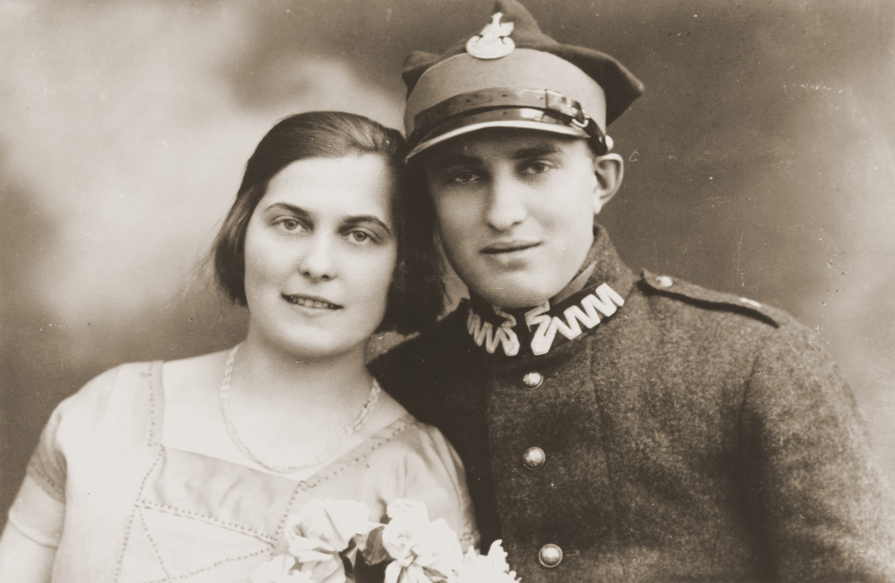 Studio portrait of two Jewish siblings in Zarki.  Pictured are Tola and Moszek Broda.  Moszek is in the uniform of the Polish army.