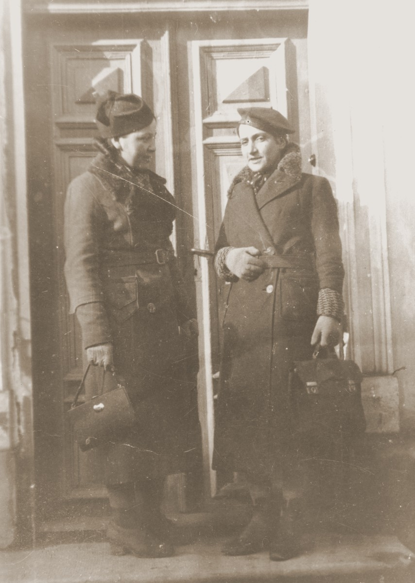 Two Jewish sisters pose outside a door in Lancut, Poland.  Pictured are Ita Gurfein (left) and Faige (Gurfein) Gersten (right).