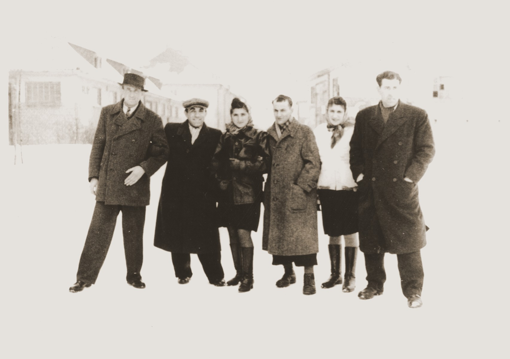 Group portrait of Jewish DPs standing in the snow in the Bergen-Belsen displaced persons camp.  Among those pictured are: Moishe Broda, David Marmor, Edek Goldblum and Manya (Goldblum) Marmor.