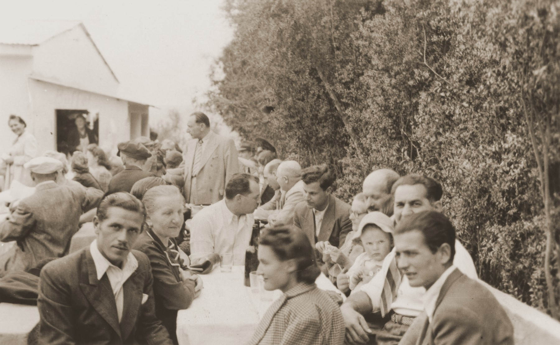 Austrian Jewish refugees in La Paz meet in a restaurant [Quinta Elma] to raise money for the victims of the Orazio shipwreck.  Among those pictured are Ferry Kohn (front, left); Lina Spitzer (behind Kohn); Rosie Spitzer (front, center); Julius Wolfinger (front, right); Eugen Spitzer (holding baby Leo); and Nathan Wolfinger (behind Leo).
